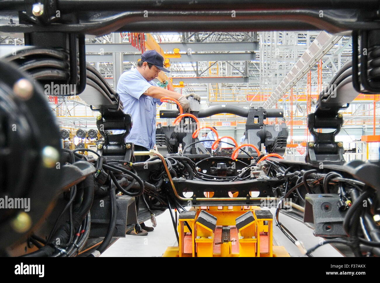 (151001)--XINGTAI, 1. Oktober 2015 (Xinhua)--Arbeiter installieren einen schweren Lkw auf einer Produktionsbasis Stockbild