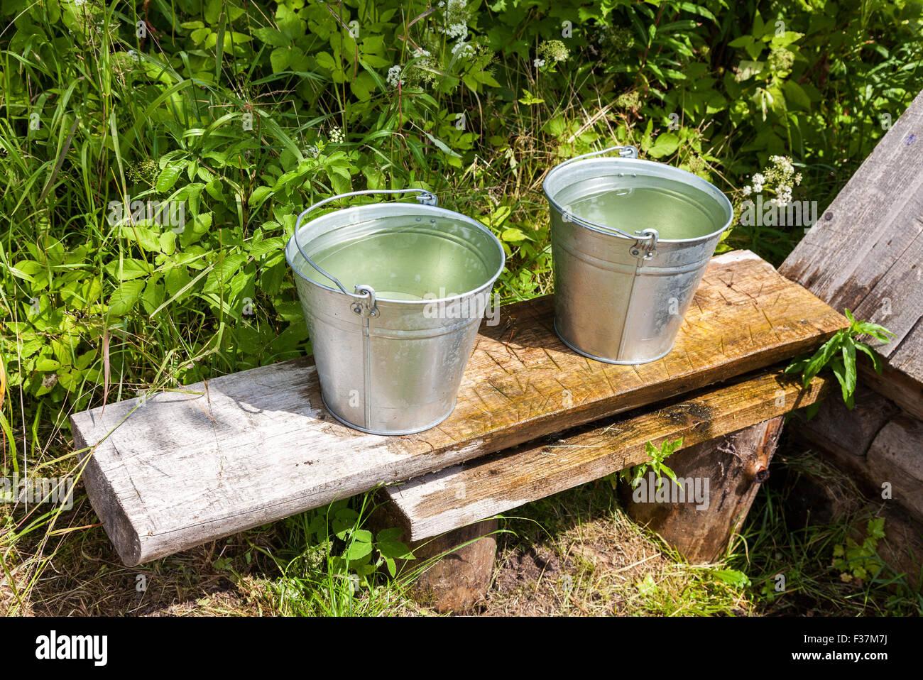 Eimer Wasser stehend auf einer Bank am Dorf Wasser gut Stockbild