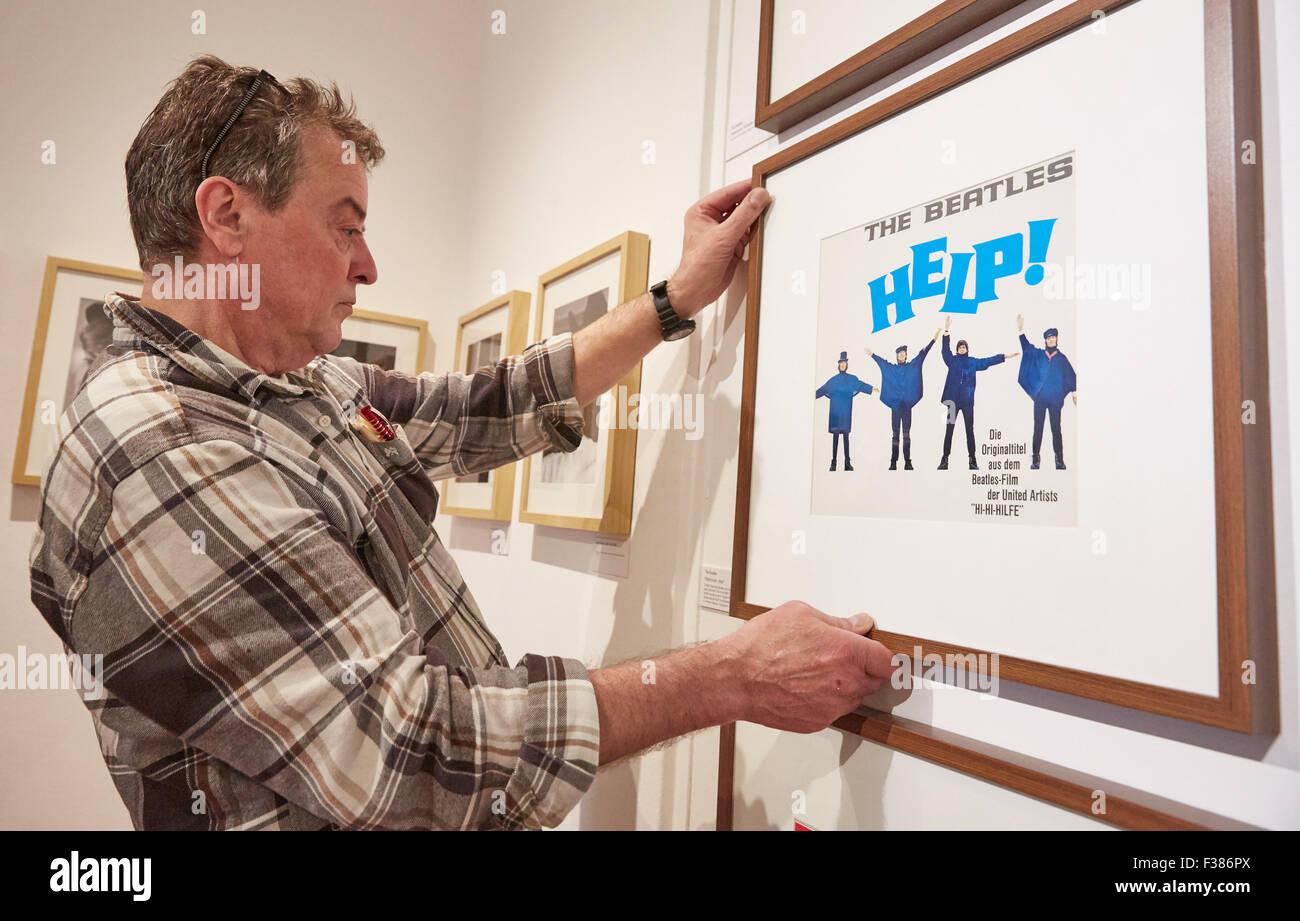 Technischer Assistent Klaus Volcsik auflegt die Plattencover für Hilfe! von den Beatles John Lennon - Ausstellung Stockbild