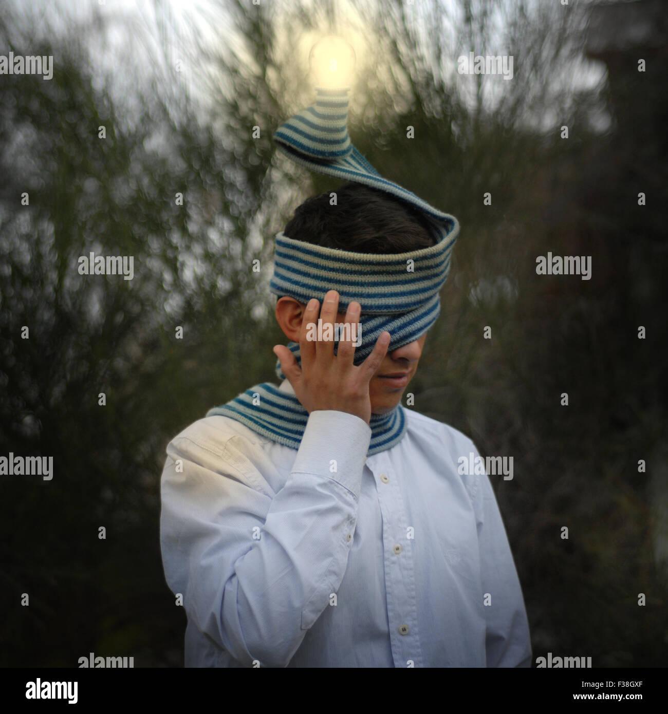 Junge mit Gesicht mit einem blauen Schal und einem beleuchteten Fokus versteckt Stockfoto