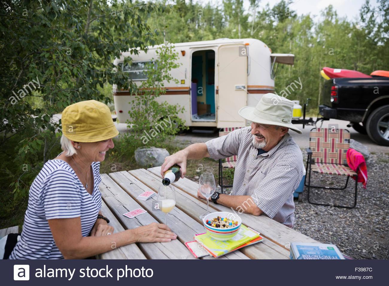 Älteres paar trinken Sekt Apfelwein-Campingplatz-Picknick-Tisch Stockbild