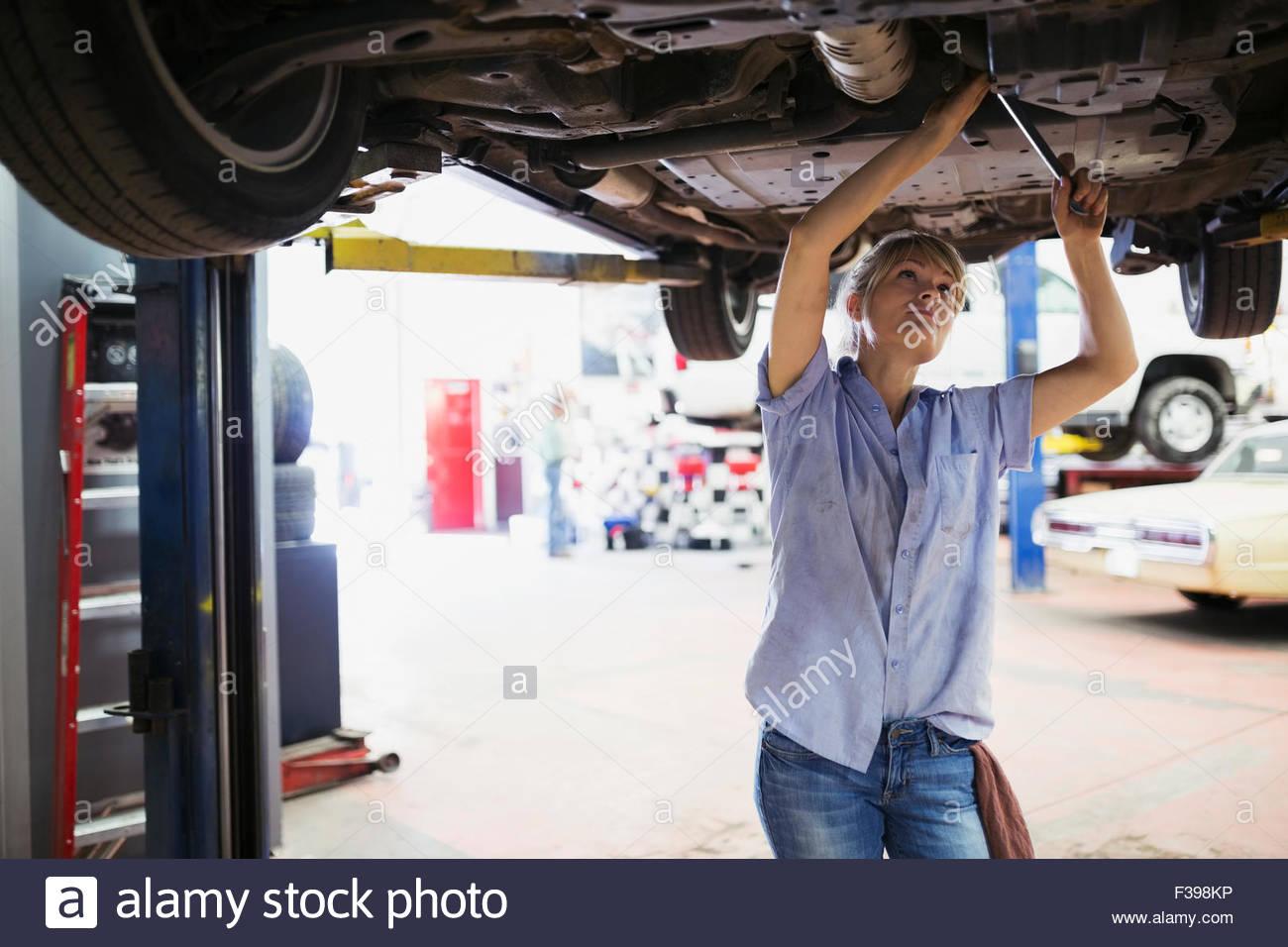 Weibliche Mechaniker arbeiten unter Auto-Auto-Werkstatt Stockbild