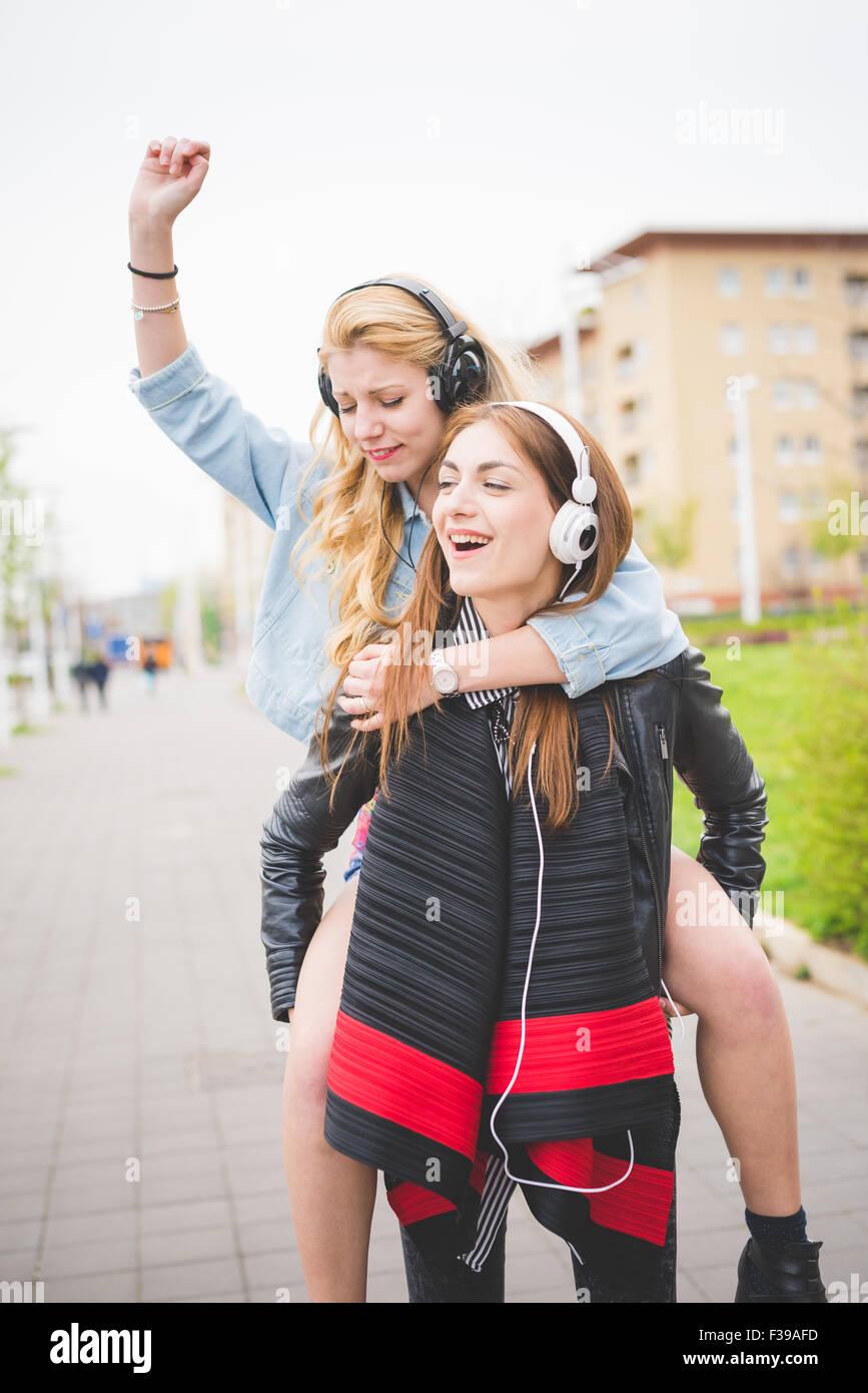 Knie-Abbildung von zwei junge Blonde und Brünette Mädchen anhören von Musik in der Stadt Spaß, Stockbild