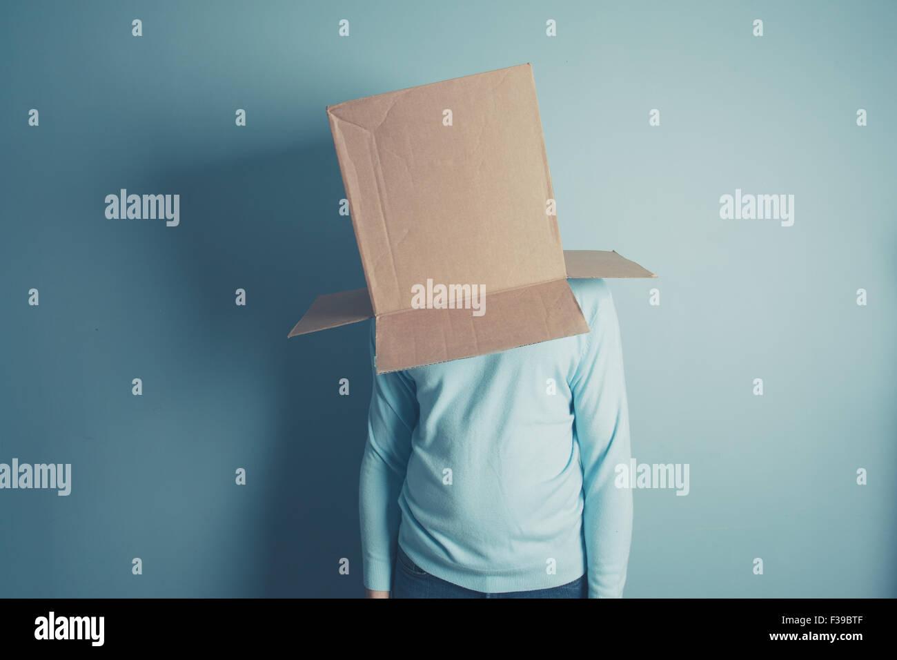 Ein Mann steht mit einem Karton über dem Kopf Stockbild