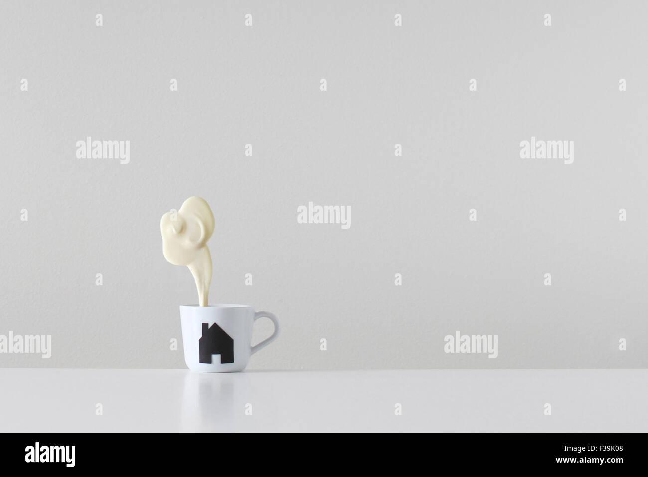 Home Brew gemacht Teetasse mit Haus Silhouette Druck und Dampf aus weißer Schokolade kommt aus dem Schornstein Stockbild