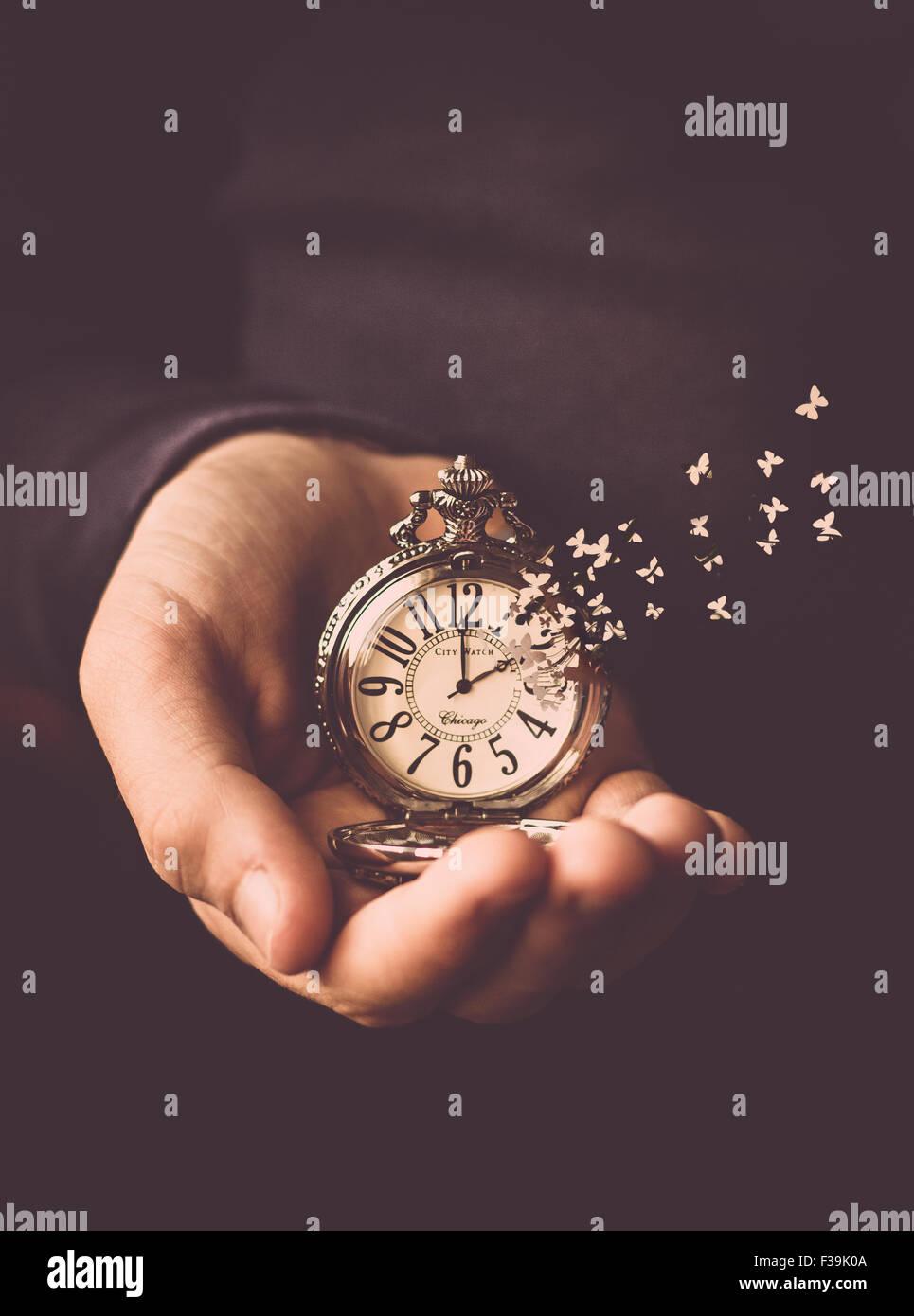 Mann, der eine Uhr mit der Zeit aus dem Zifferblatt wie Schmetterlinge fliegen in seiner Hand hältStockfoto