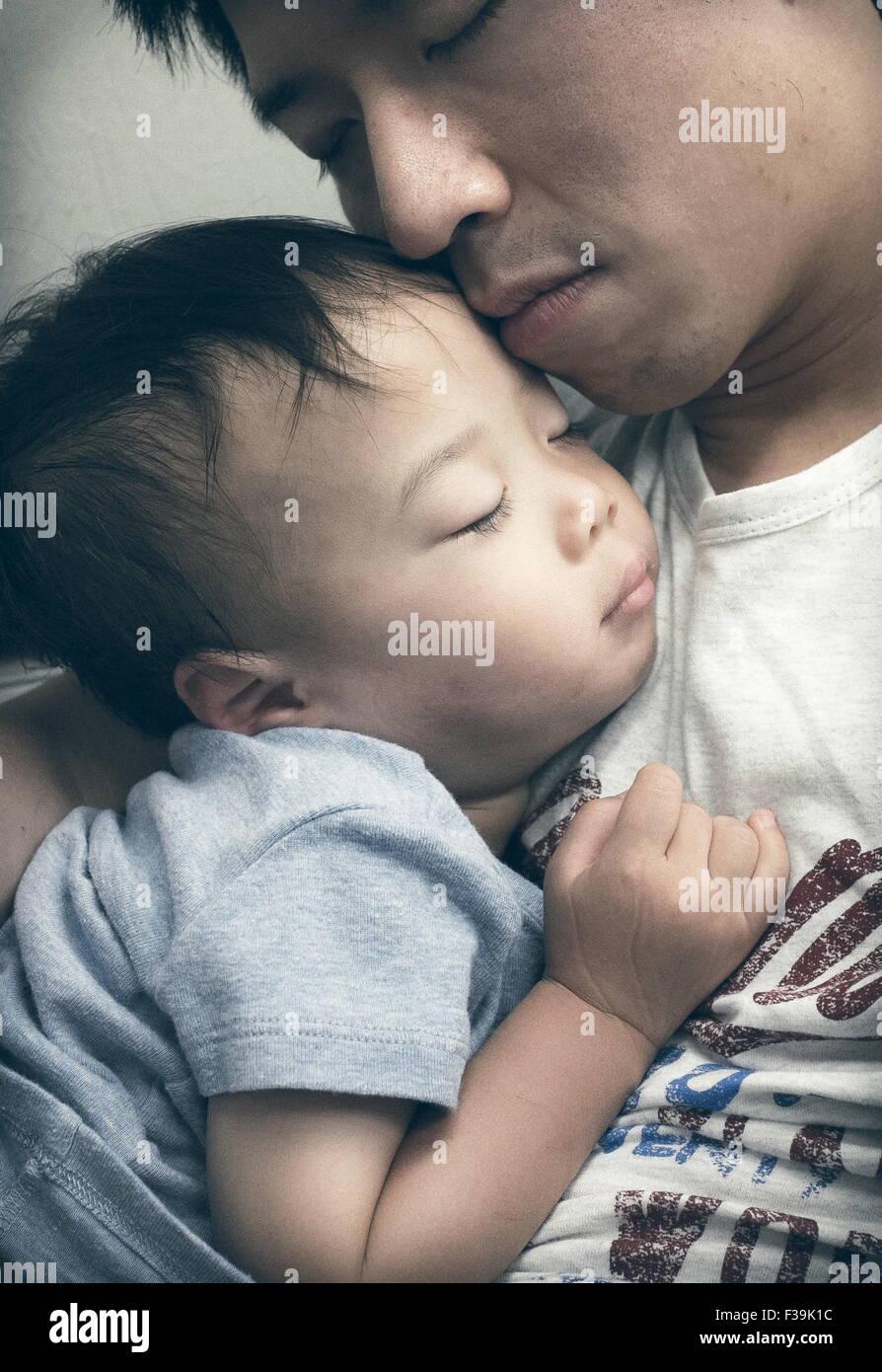 Jungen schlafen in des Vaters Schoß Stockbild