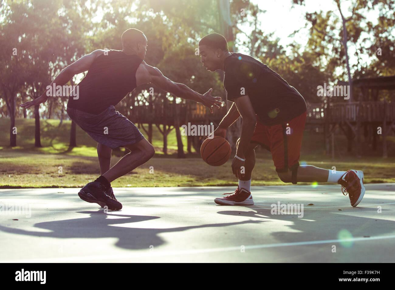 Zwei junge Männer spielen Basketball im Park bei Sonnenuntergang Stockfoto
