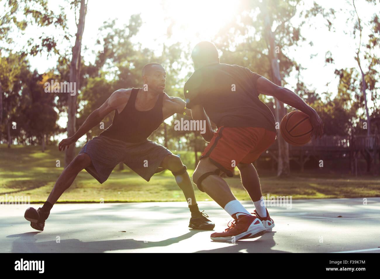 Zwei junge Männer spielen Basketball im Park bei Sonnenuntergang Stockbild