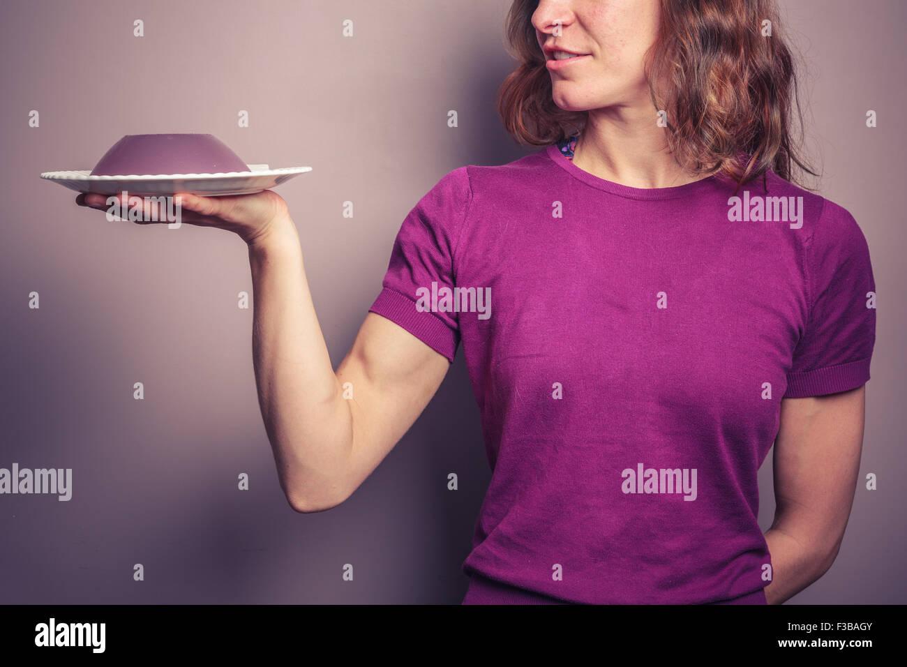 Eine junge Frau in einem lila Top präsentiert einen Teller mit Gelee Stockbild