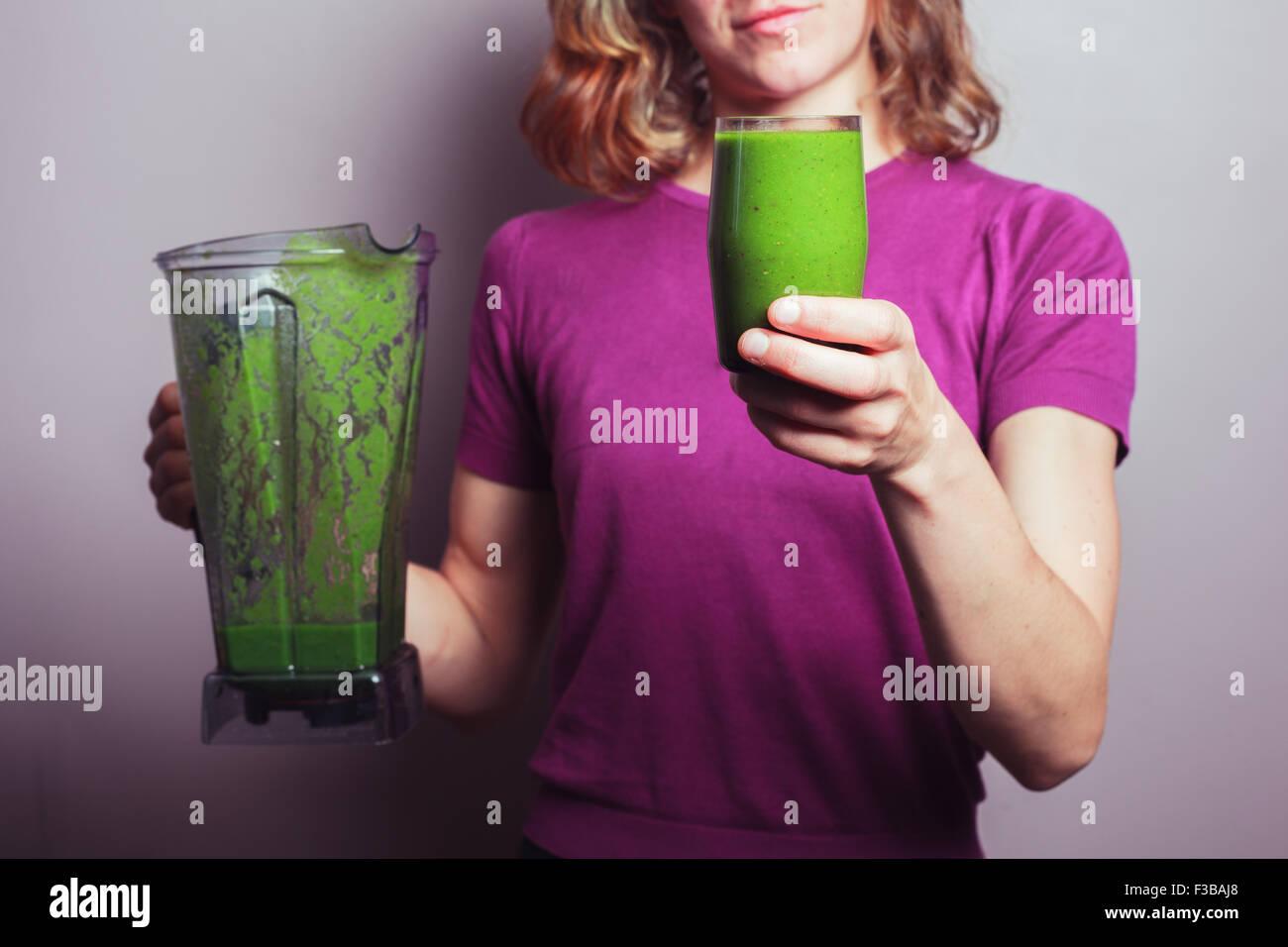 Eine junge Frau in einem lila Top hält ein Mixer und ein Glas mit grünen Frucht-smoothie Stockbild