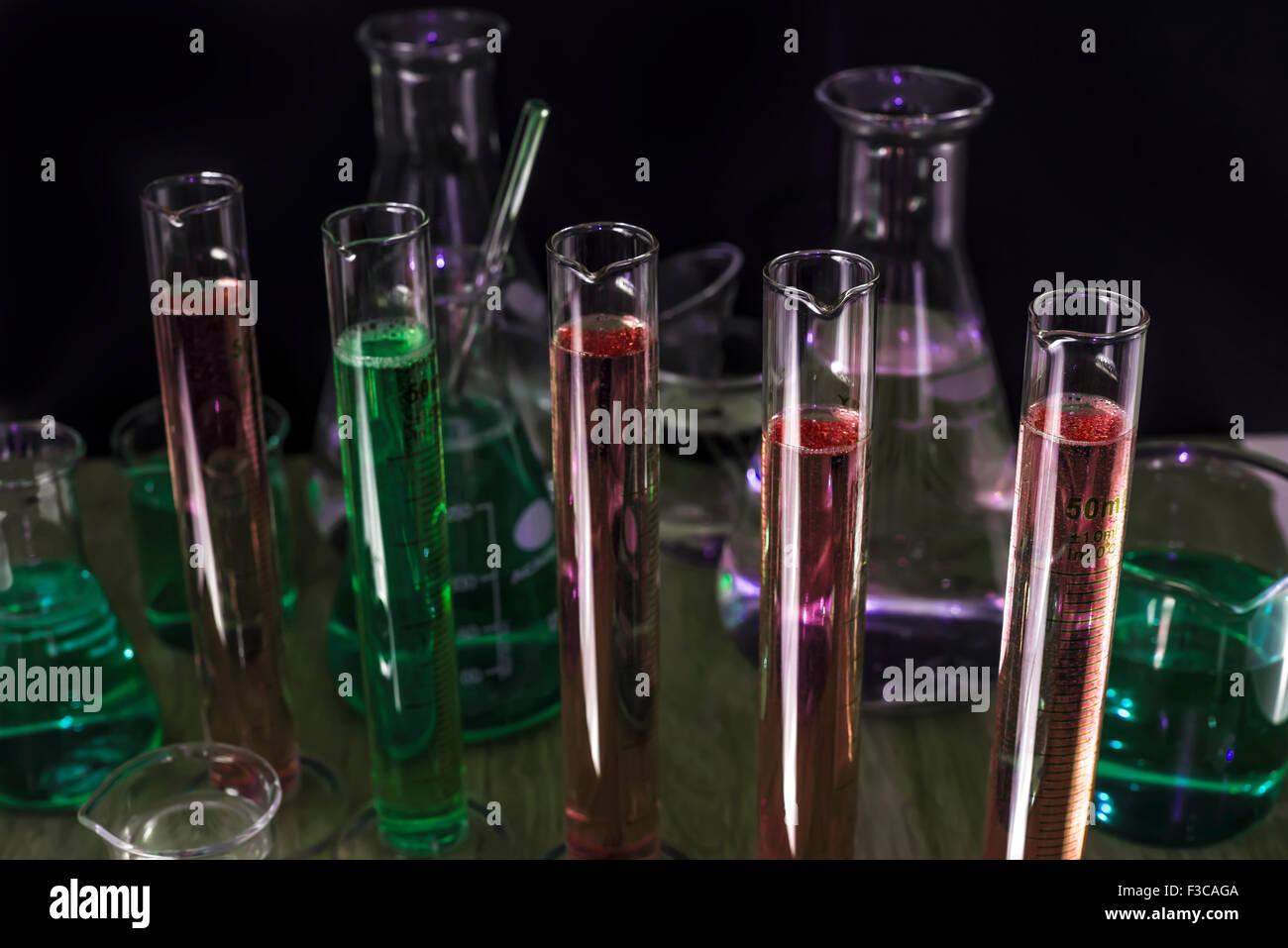 Chemie-Reagenzgläser und Kolben in einem dunklen Labor Stockbild