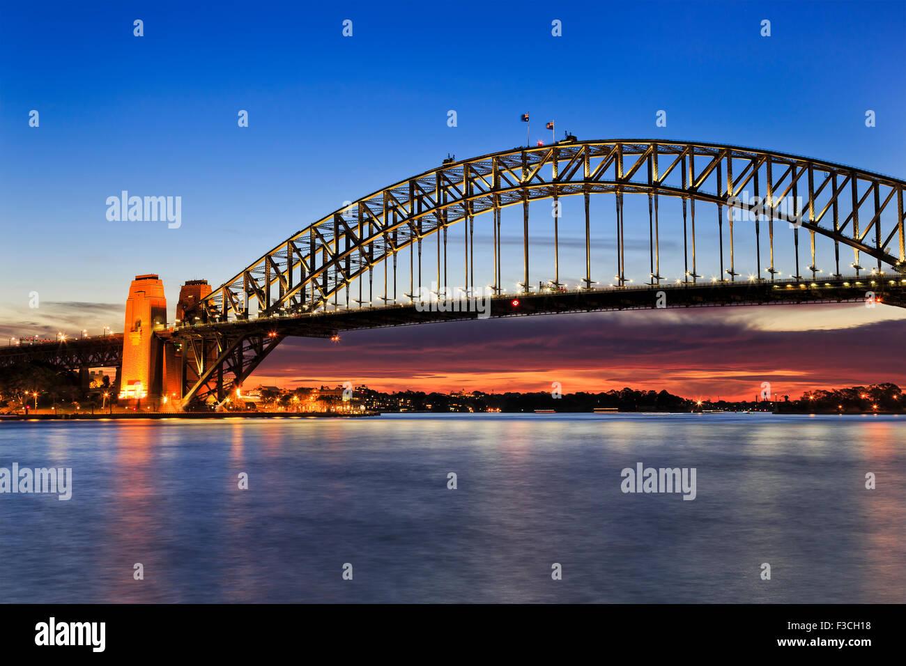 Seitenansicht der Sydney Harbour Bridge bei Sonnenaufgang mit Scarlett Sonnenlicht und Beleuchtung noch Bogen Stockbild