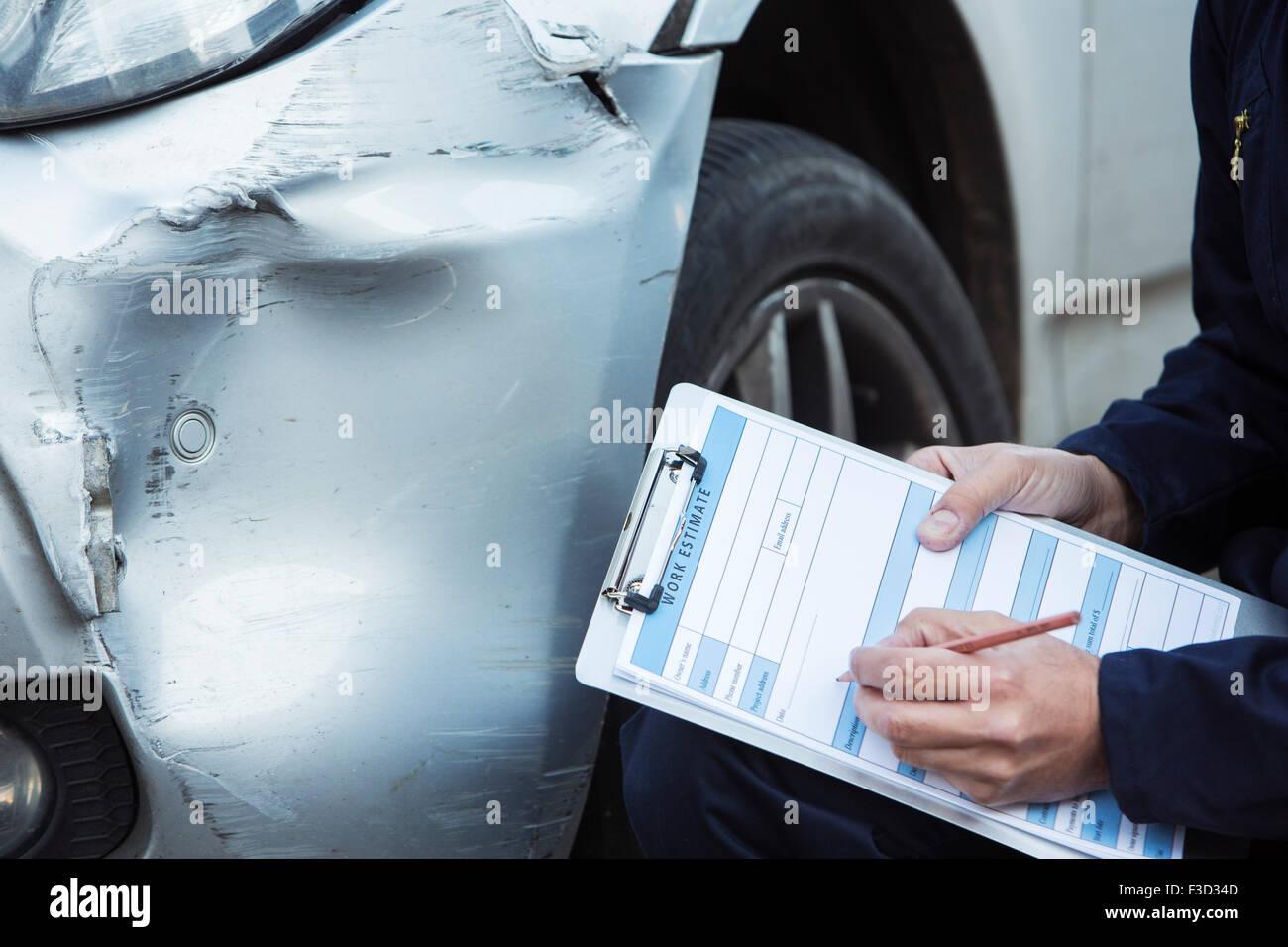 Automechaniker Workshop Inspektion Schäden an Fahrzeug und Reparatur Kostenvoranschlag ausfüllen Stockfoto
