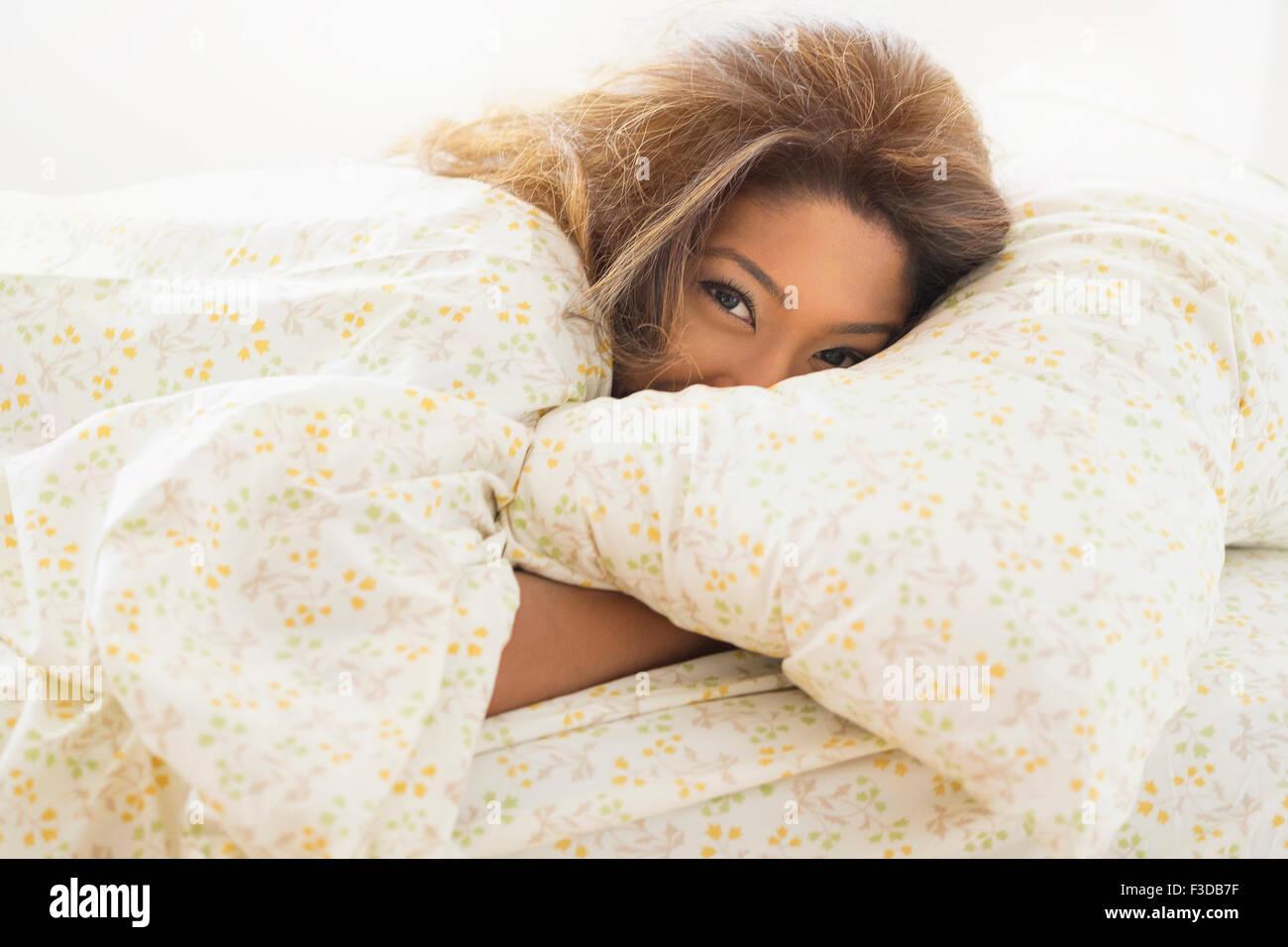 Junge Frau im Bett liegend Stockbild