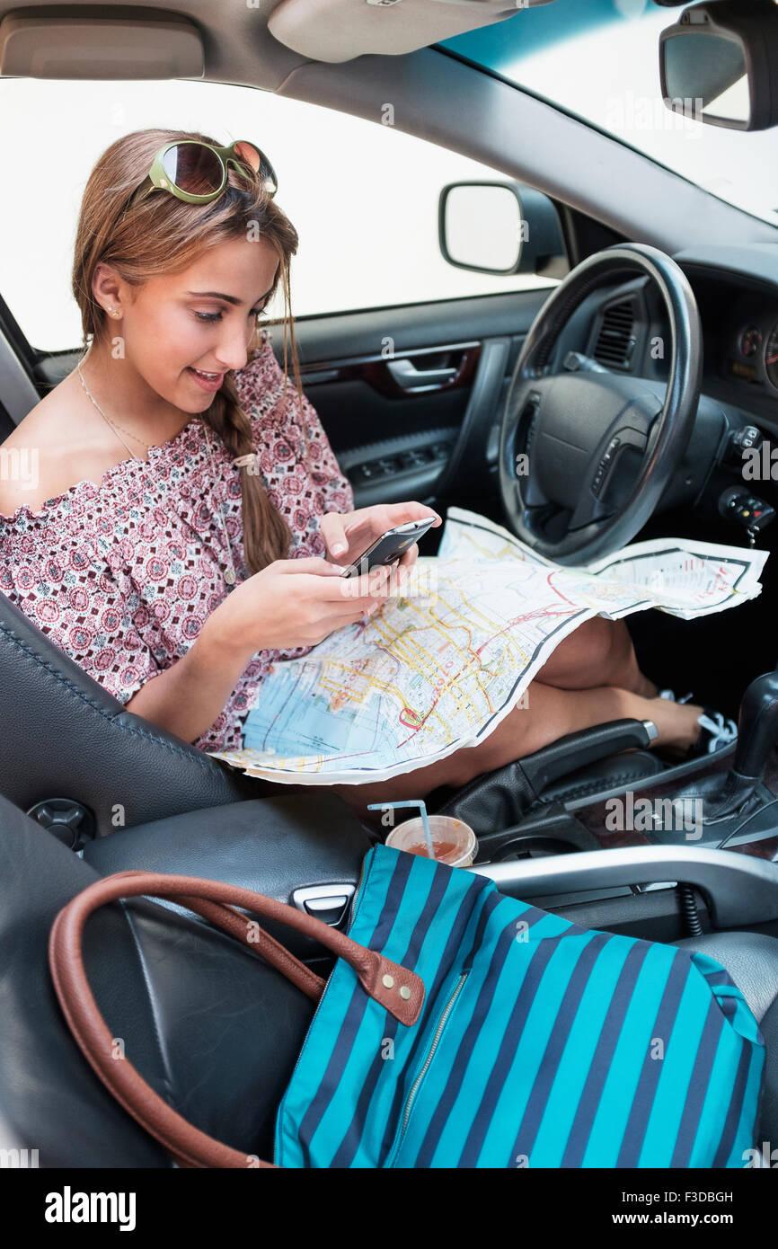 Frau überprüft Telefon im Auto mit Karte auf Schoß Stockbild