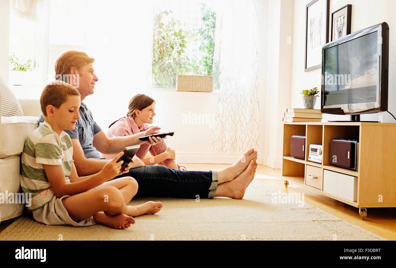 Kinder (8-9, 10-11) vor dem Fernseher mit ihrem Vater Stockbild
