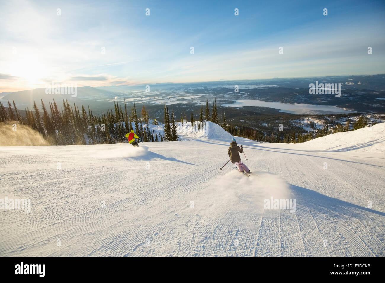 Zwei Personen auf der Skipiste im Sonnenlicht Stockbild