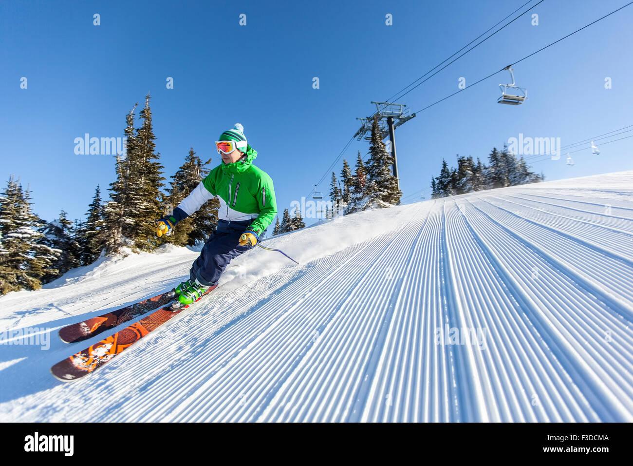 Reifer Mann auf Skipiste unter blauem Himmel Stockbild