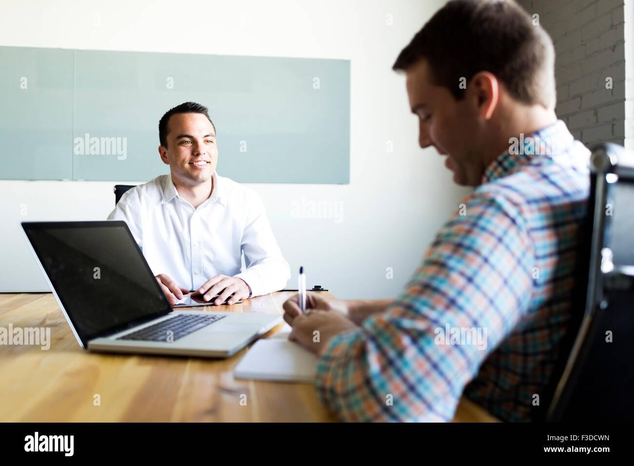 Mann interviewt im Konferenzraum Stockbild