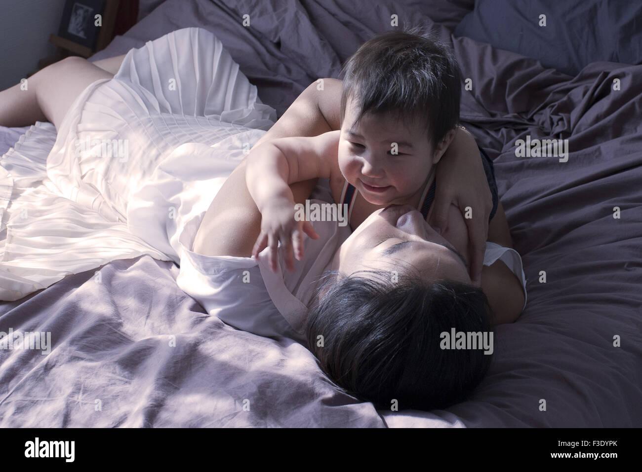 Mutter und Baby Boy auf Bett gemeinsam entspannen Stockbild