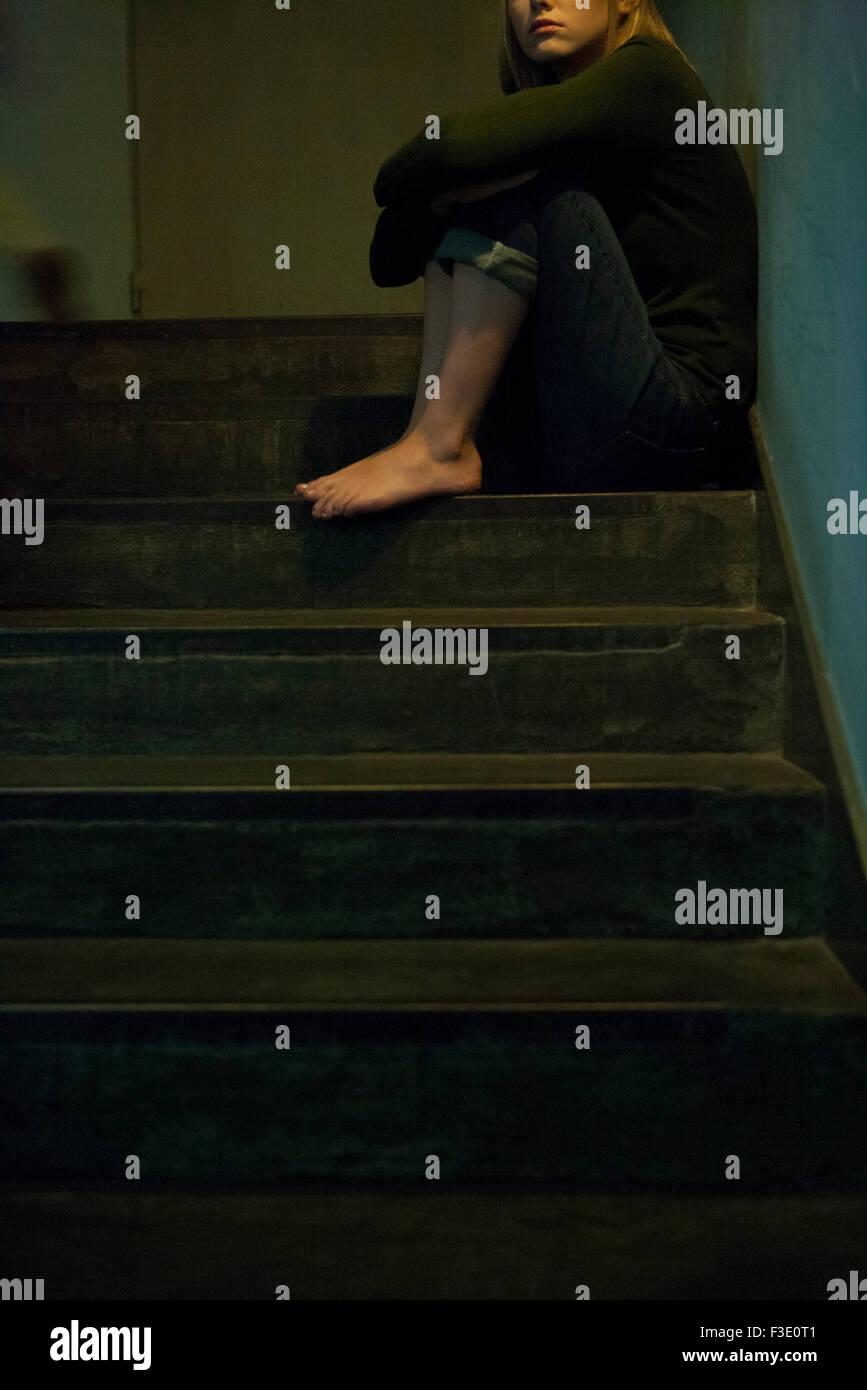 Frau sitzt allein im Treppenhaus Stockbild