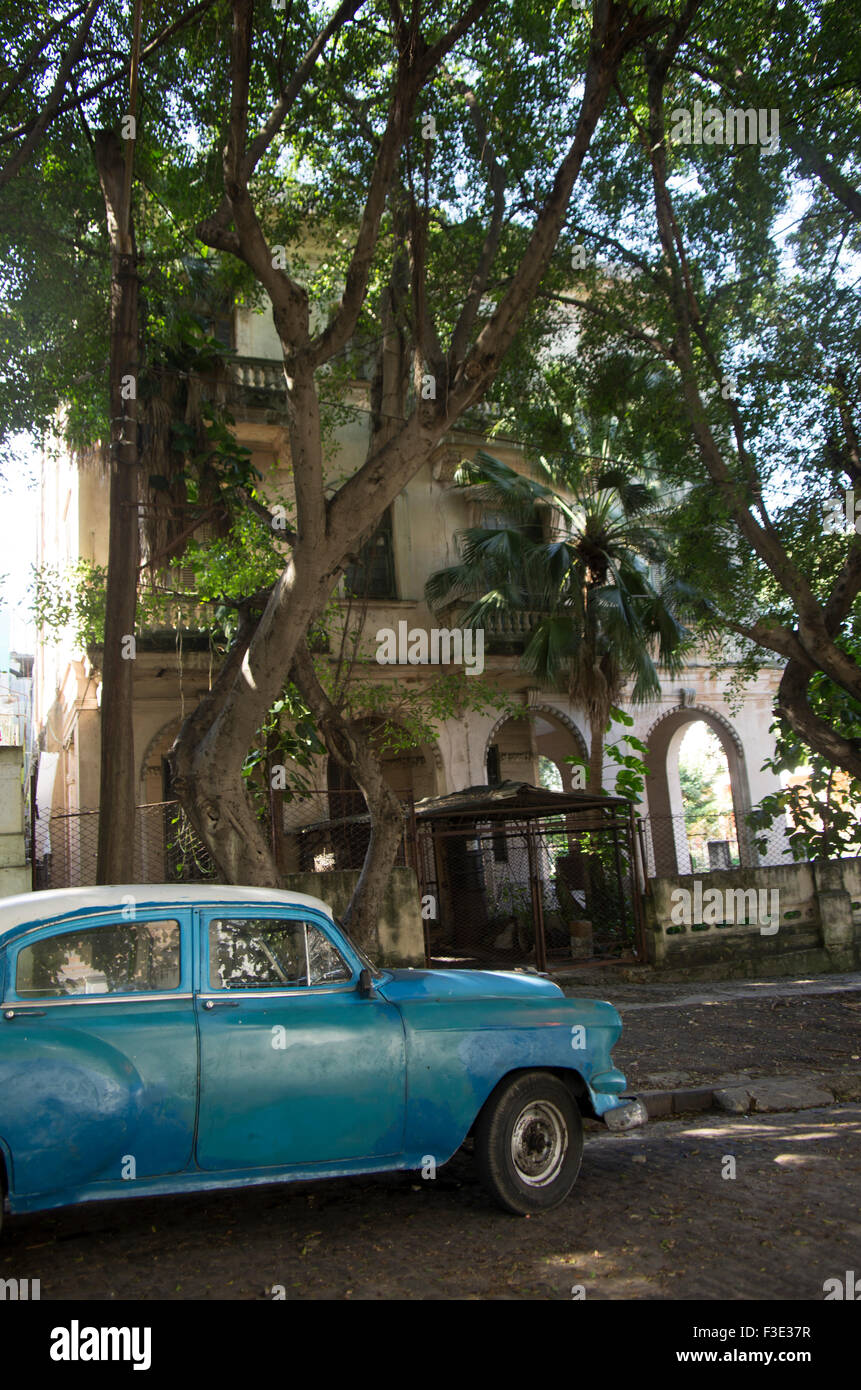 Antike American Vintage blaues Auto parkte vor einem Herrenhaus auf einer schattigen Straße in Havanna, Republik Stockfoto