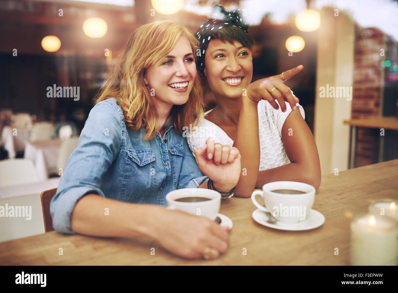 Glücklich Freundinnen genießen Kaffee zusammen in einem Kaffeehaus sitzen zeigen und lächelt amüsiert, Stockbild
