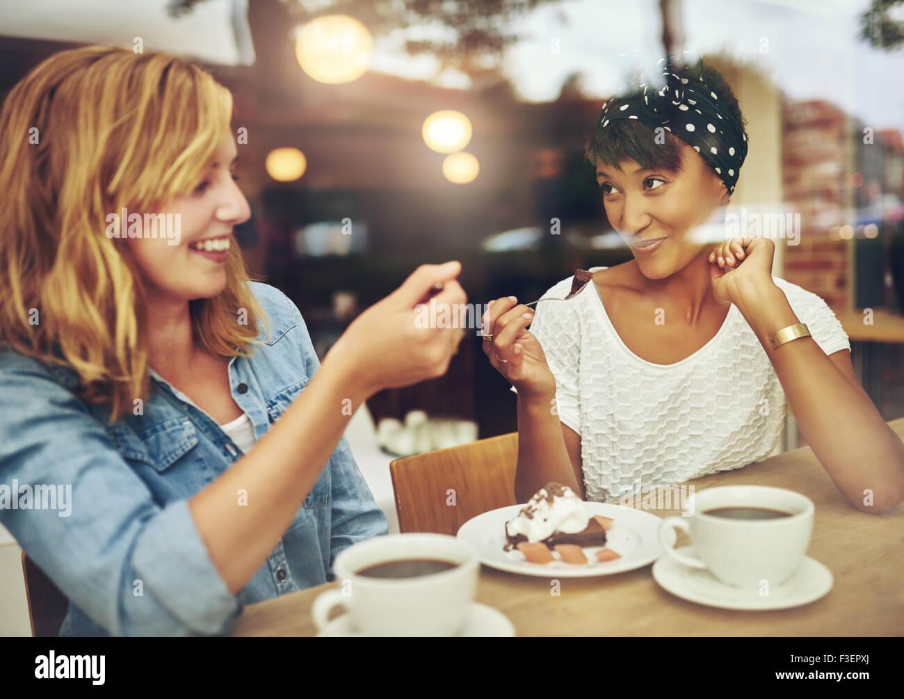 Zwei charismatische Multi ethnischen junge Freundinnen sitzen an einem Schalter in einem Café eine Tasse Kaffee Stockbild