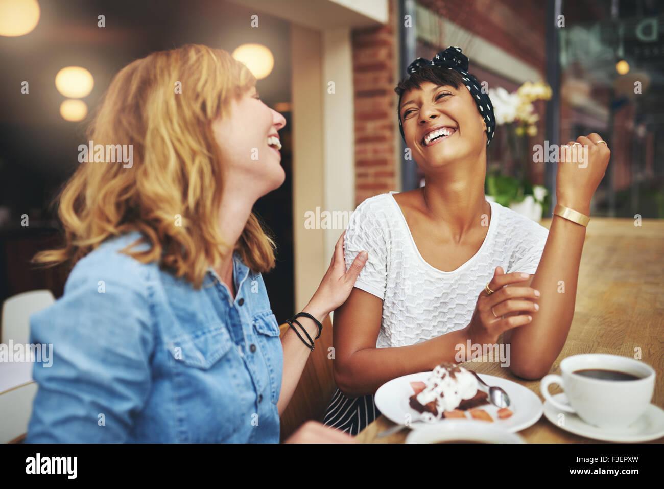 Zwei multiethnischen Junge weibliche Freunde Kaffee zusammen in einem Restaurant, Lachen und Scherzen berühren Stockbild