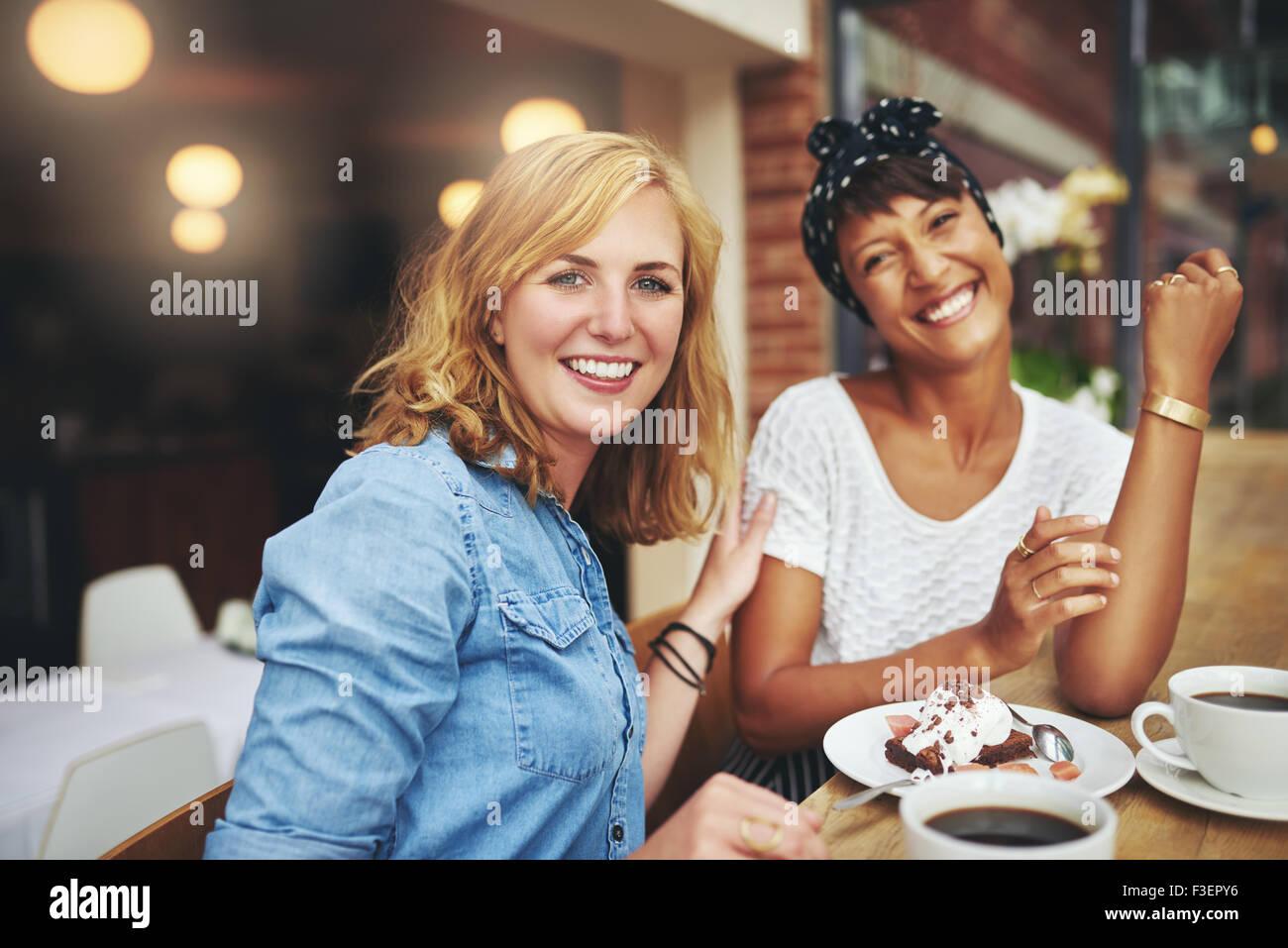 Zwei attraktiven jungen multiethnischen weibliche Freunde genießen Sie Kaffee und Kuchen in der Cafeteria glücklich Stockbild