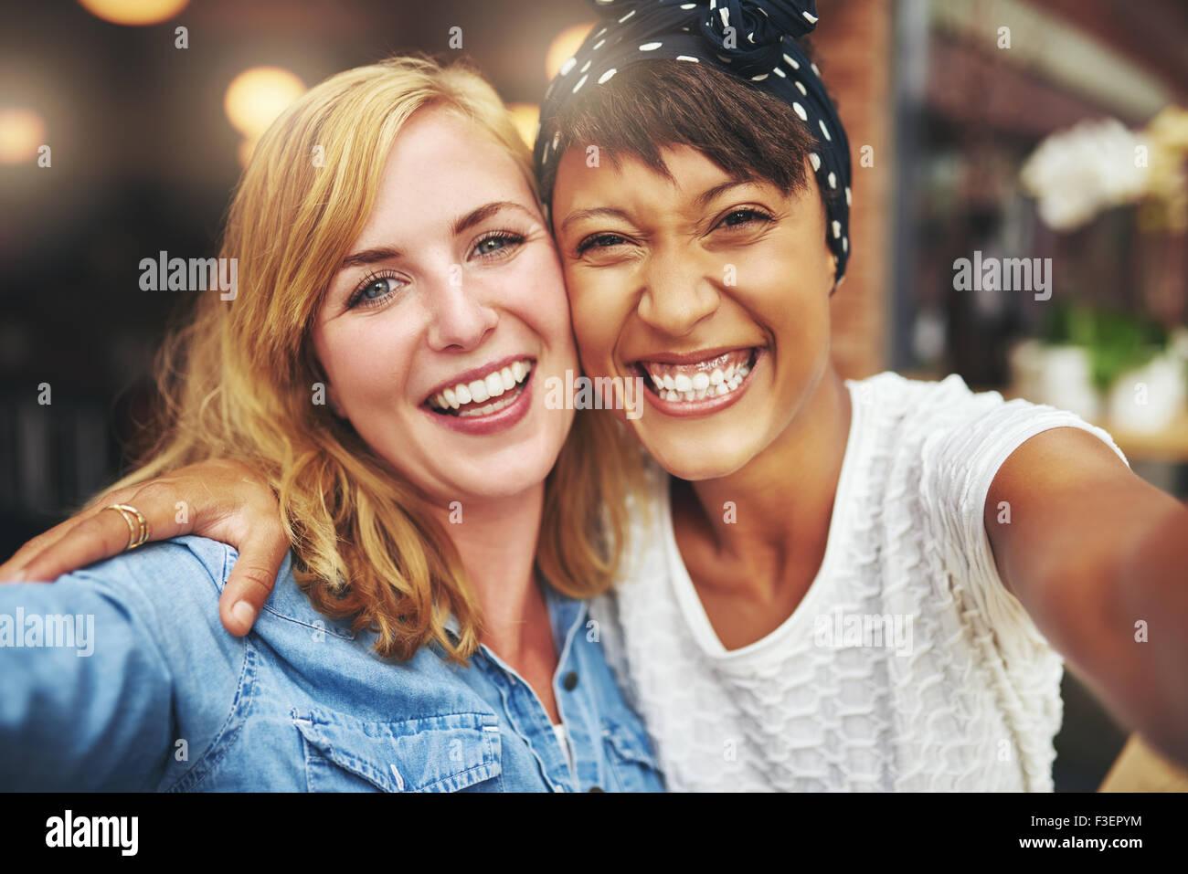 Gerne lebhafte attraktive junge Multirassischen Freundinnen glücklich grinsend in die Kamera, wie sie Arm in Stockbild