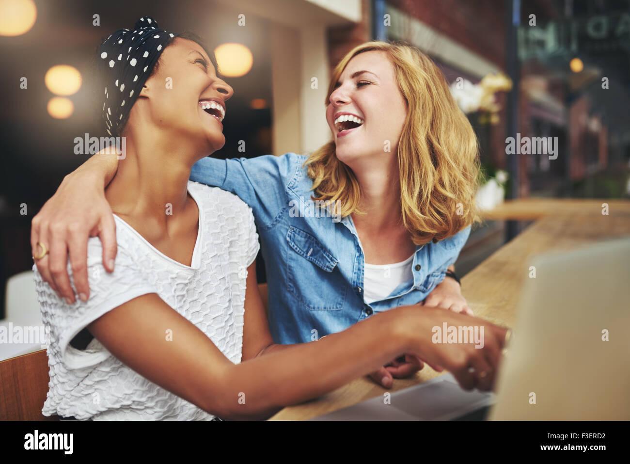 Zwei liebevolle multirassische Freundinnen umarmen und lachen, als sie auf einem Laptop-Computer-Bildschirm zeigen, Stockbild