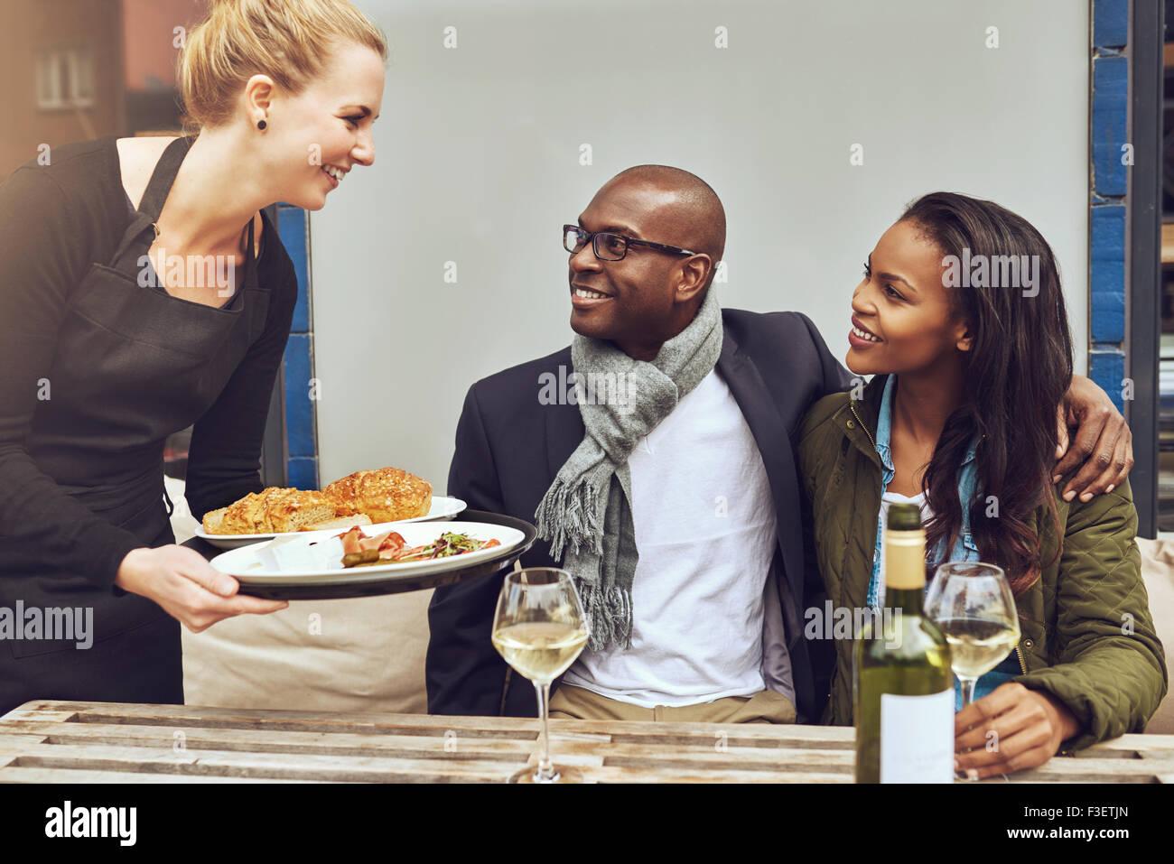 Lächelnd, glücklich junge kaukasischen Kellnerin eine liebevolle afrikanische amerikanische paar Abendessen Stockbild