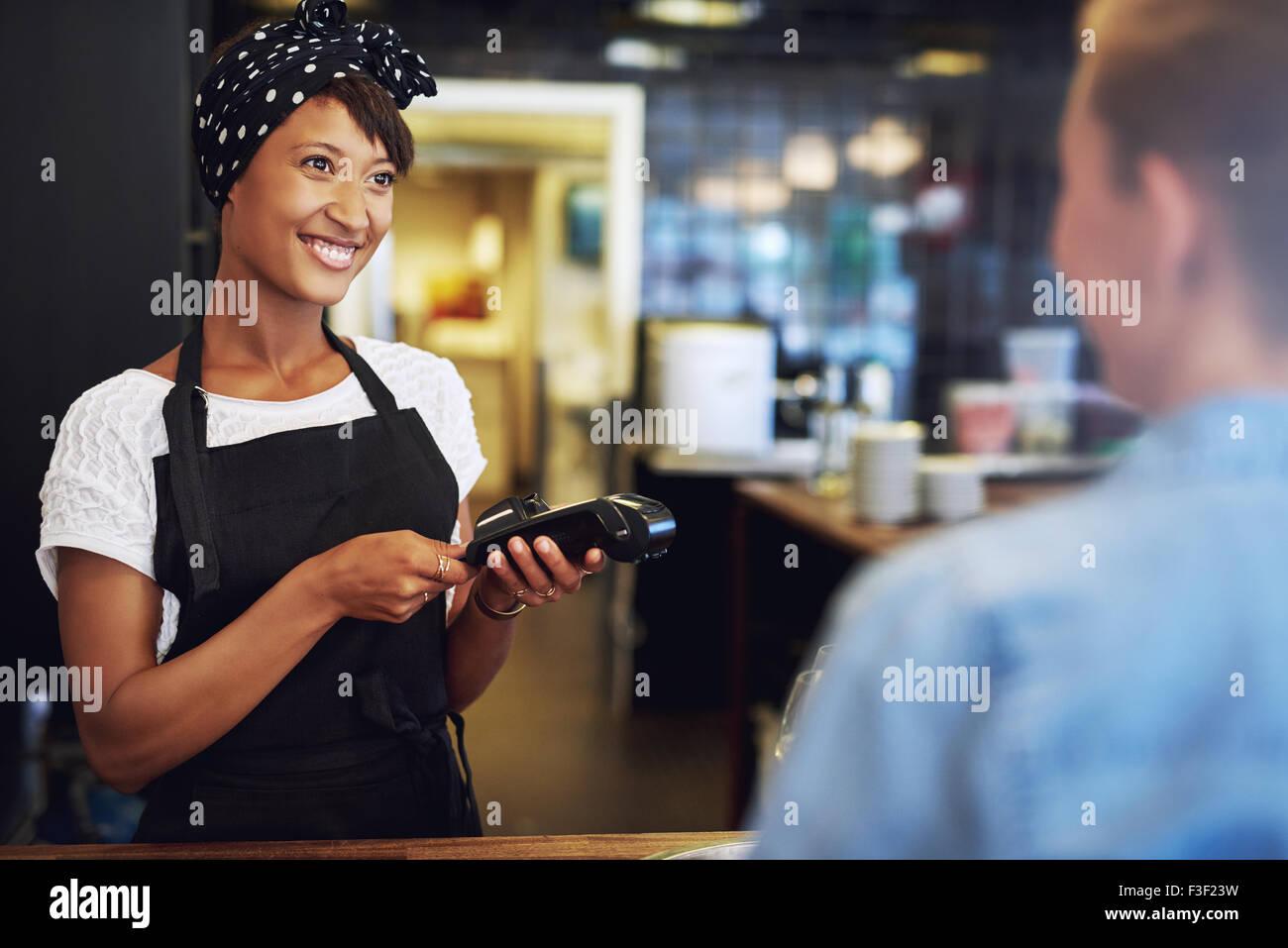 Lächelnd attraktive afrikanische amerikanische Kleinbetrieb Inhaber nehmen Zahlung von einem Kunden, die Verarbeitung Stockbild