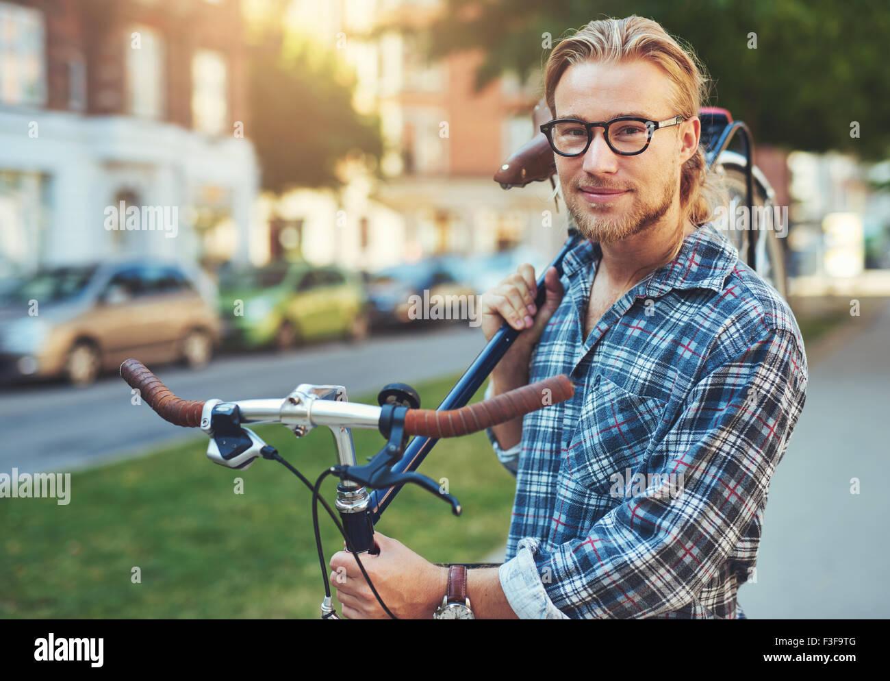 Porträt von blonden weißen Mann in der Stadt mit dem Fahrrad Stockbild
