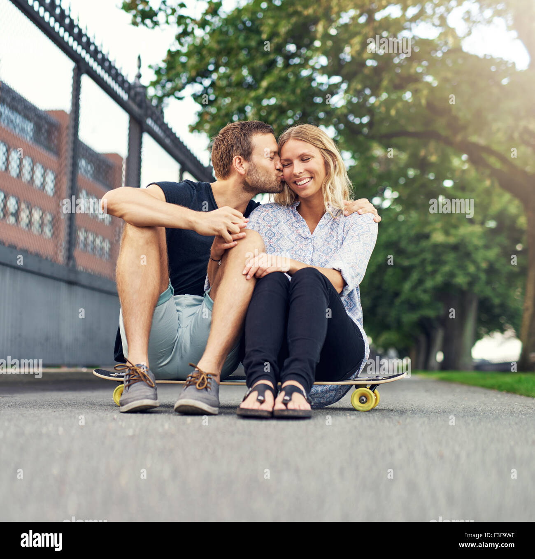 Mann auf die Wange küssen Frau sitzend in einem park Stockbild