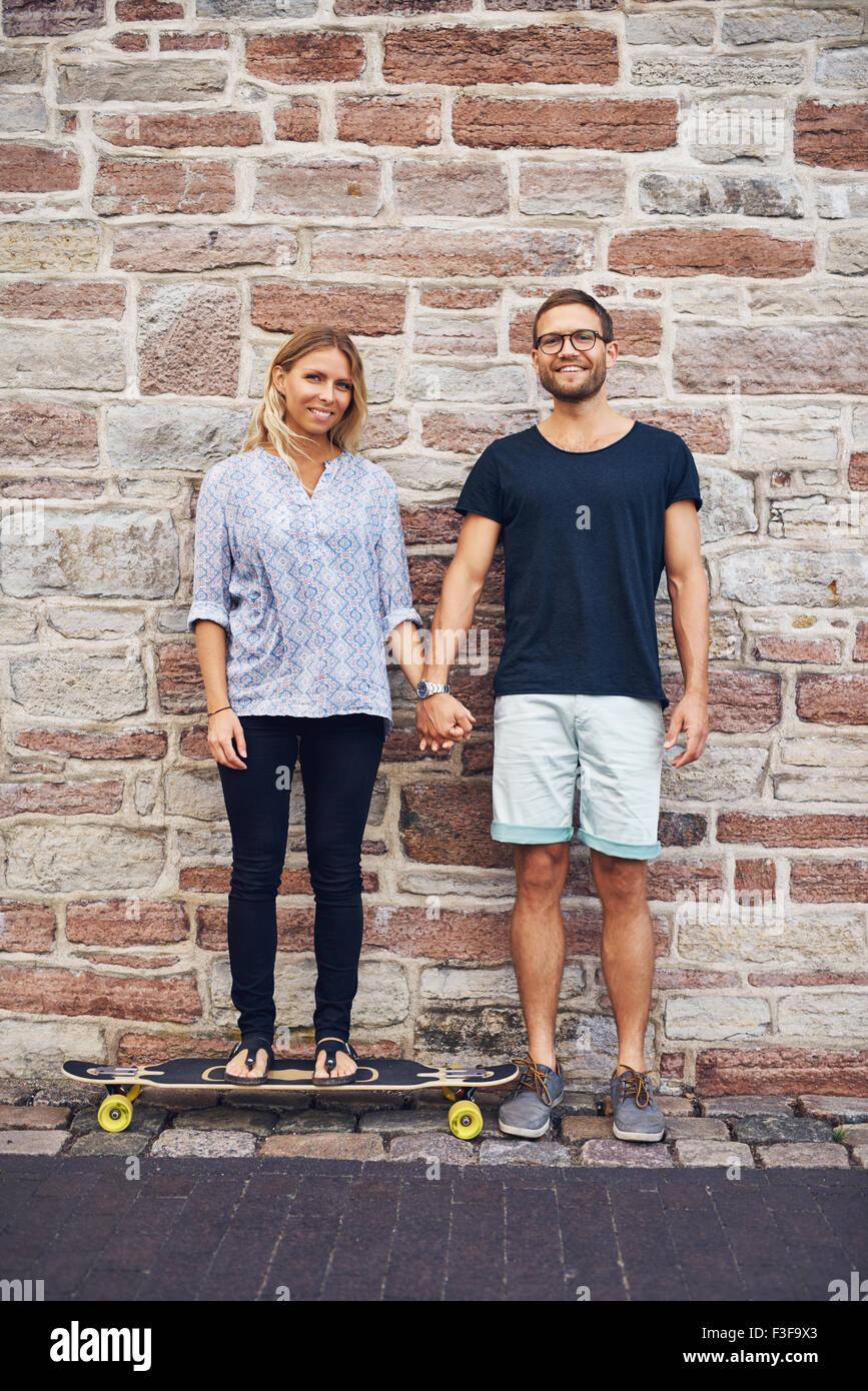 Junges Paar die Hand gegen die Wand lehnt Stockbild