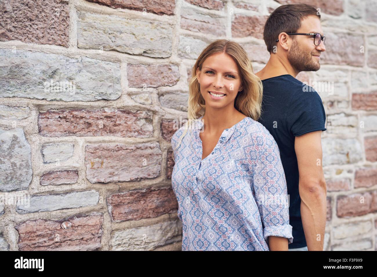 Paar steht mit dem Rücken gegen einander gegen eine Wand. Stockbild