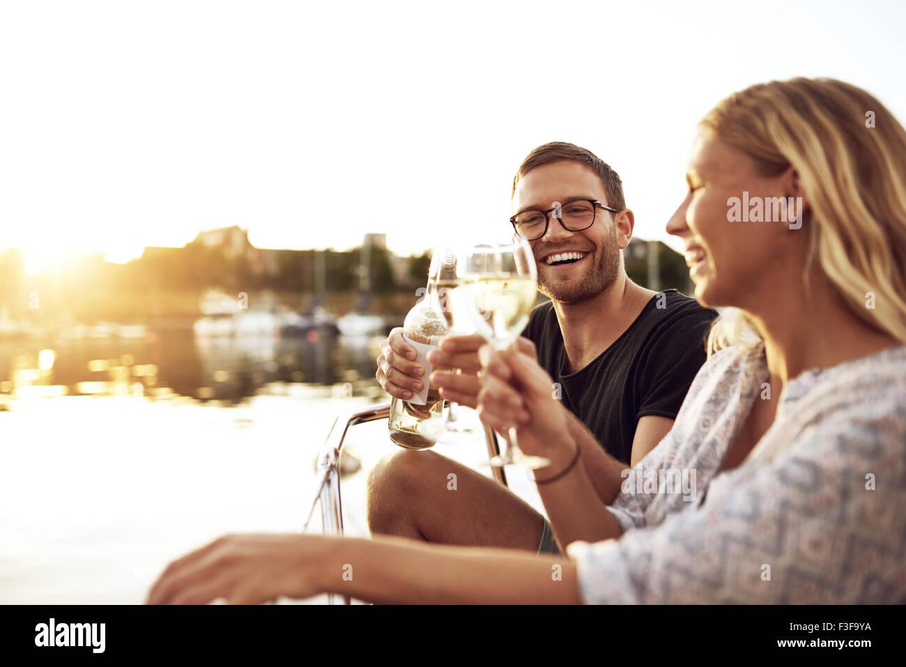Glückliches Paar toasten Gläser an einem sommerlichen Abend Stockbild