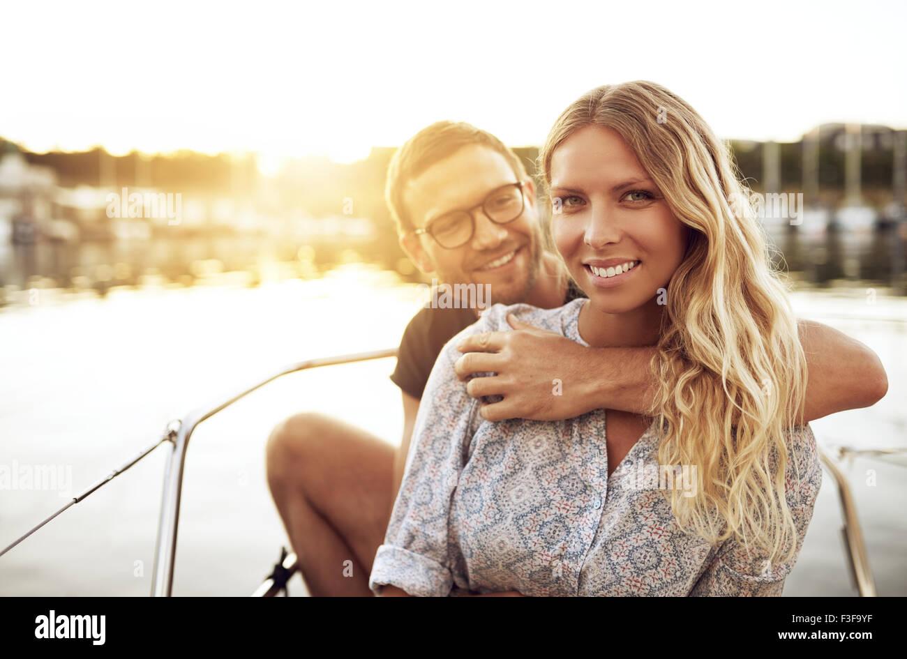 Junges Paar in Liebe draußen sitzen an einem warmen Sommertag Stockbild
