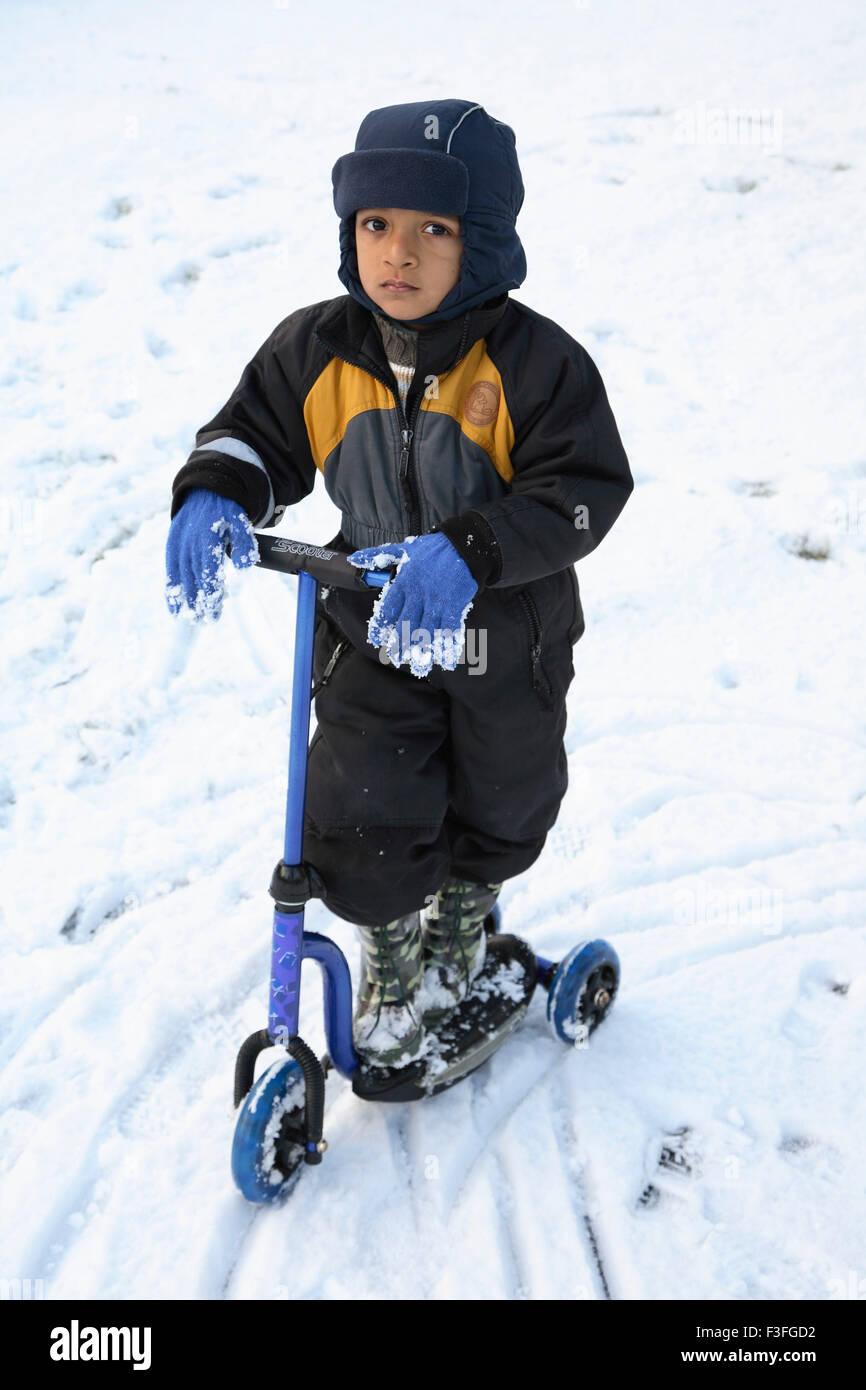 Kleiner Junge reitet seine Tri-Rad auf Schnee; Schweden Herr #468 Stockbild
