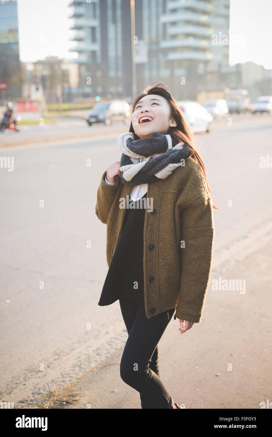 junge schöne asiatische lange braune glatte Haare Hipster in der Stadt, lachende Frau im Abendlicht - Sorglosigkeit, Stockbild
