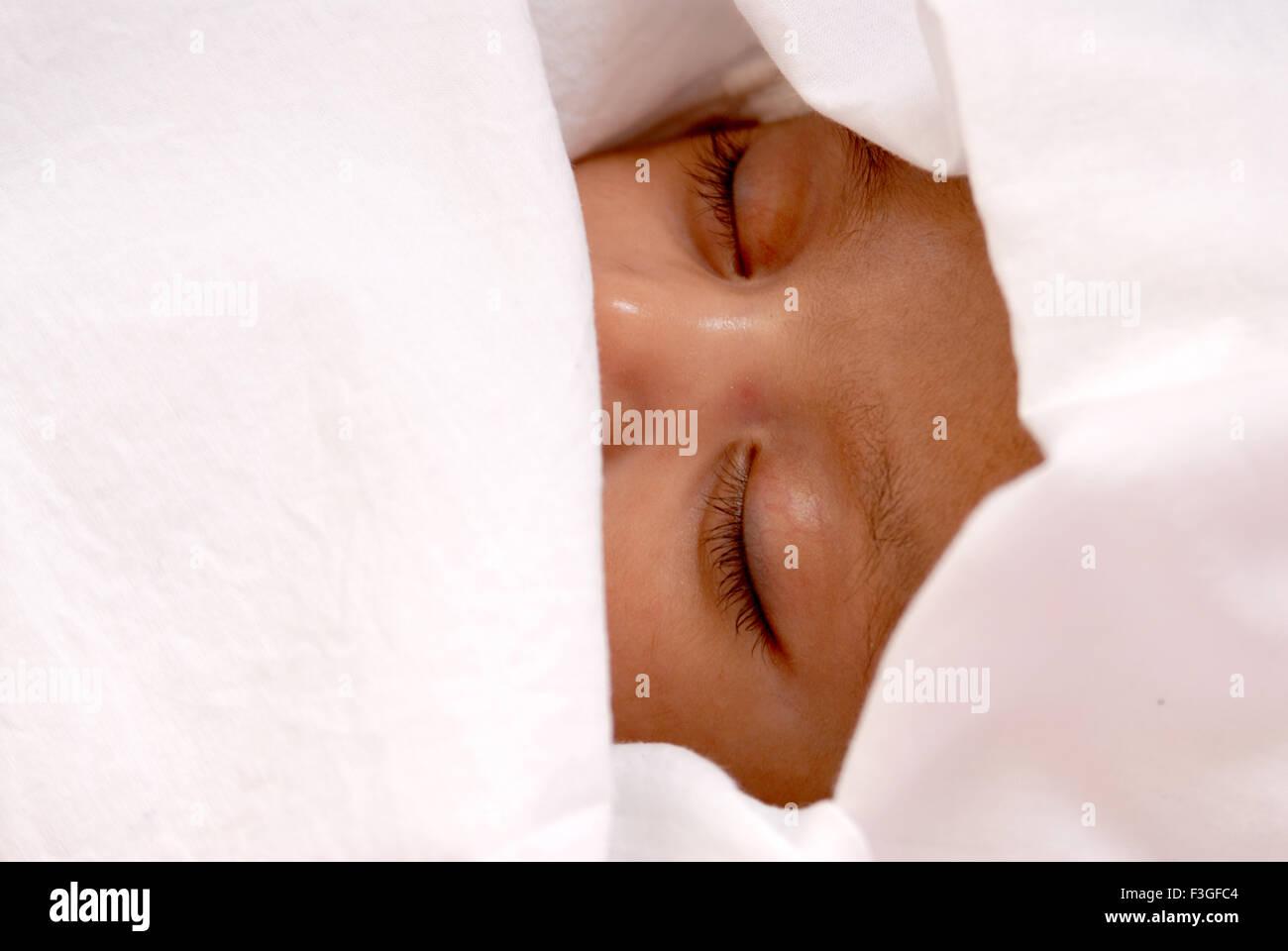 Indische Baby Mädchen Kind schlafen friedlich mit einem weißen Tuch - Herr Nr. 512-Rmm 123467 abgedeckt Stockbild