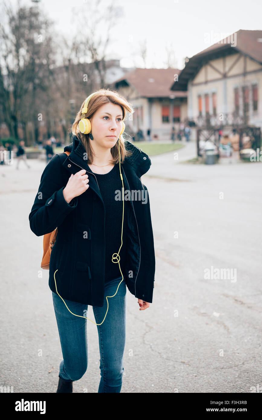 4cb6f2ef389a1 junge schöne Hipster sportliche blonde Frau zu Fuß in die Stadt Musik hören  mit Kopfhörern