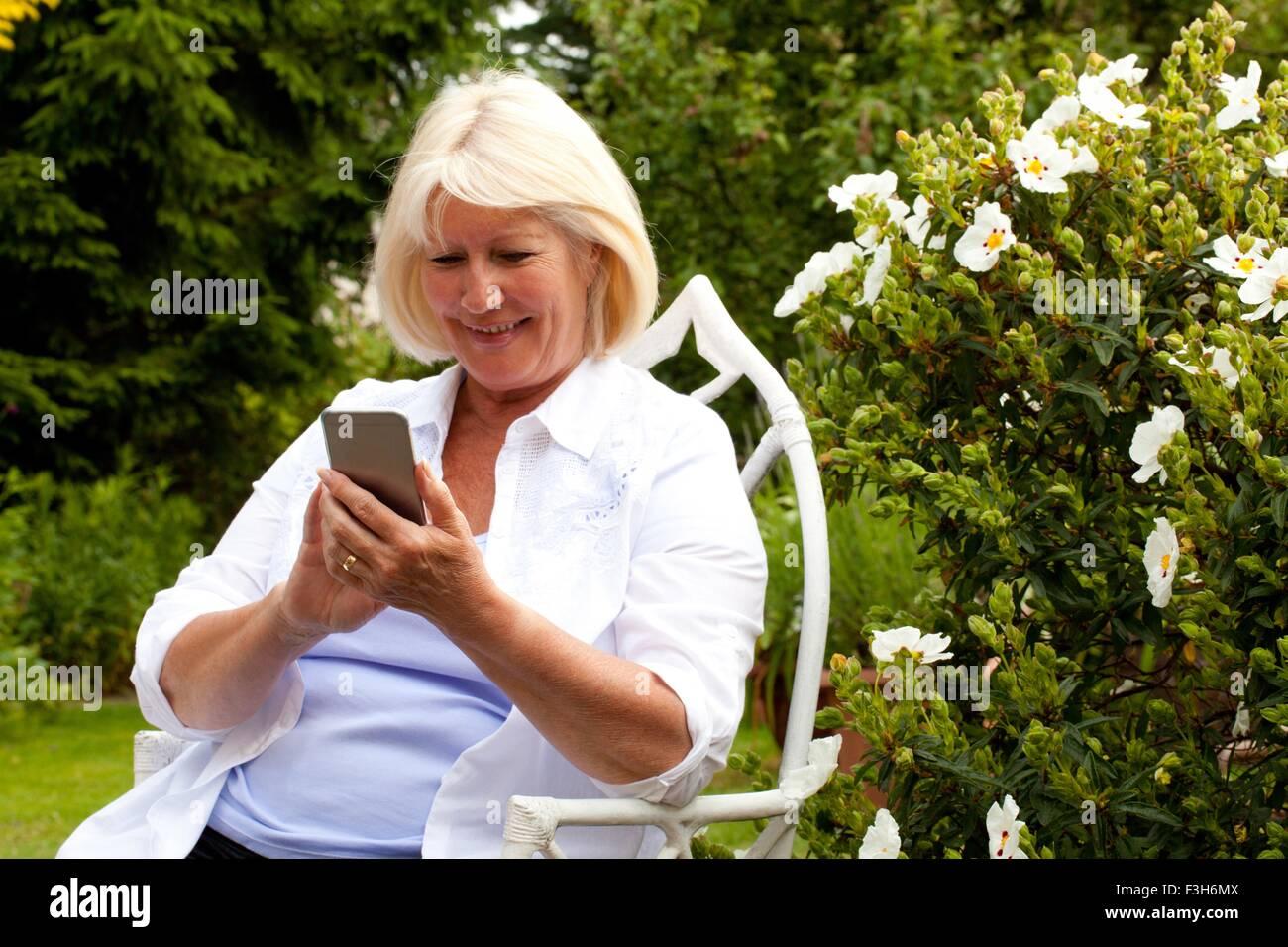 Ältere Frau im Garten mit Blick auf smartphone Stockbild