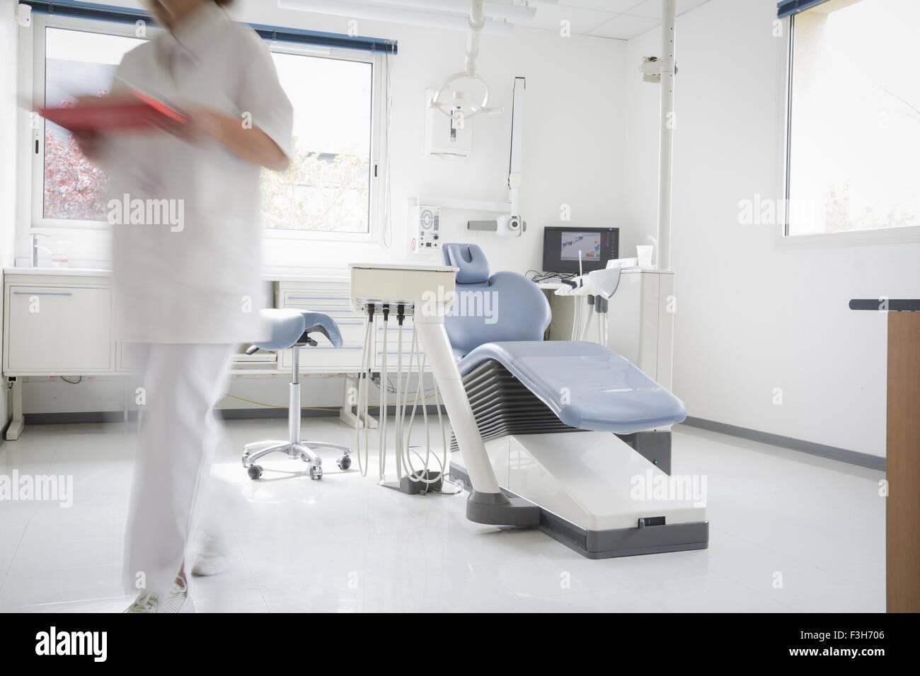 Zahnarztstuhl, Zahnarzthelferin zu Fuß entfernt, Bewegungsunschärfe Stockbild