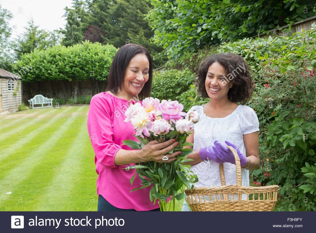Mutter und Erwachsene Tochter sammeln Blumen im Garten Stockbild
