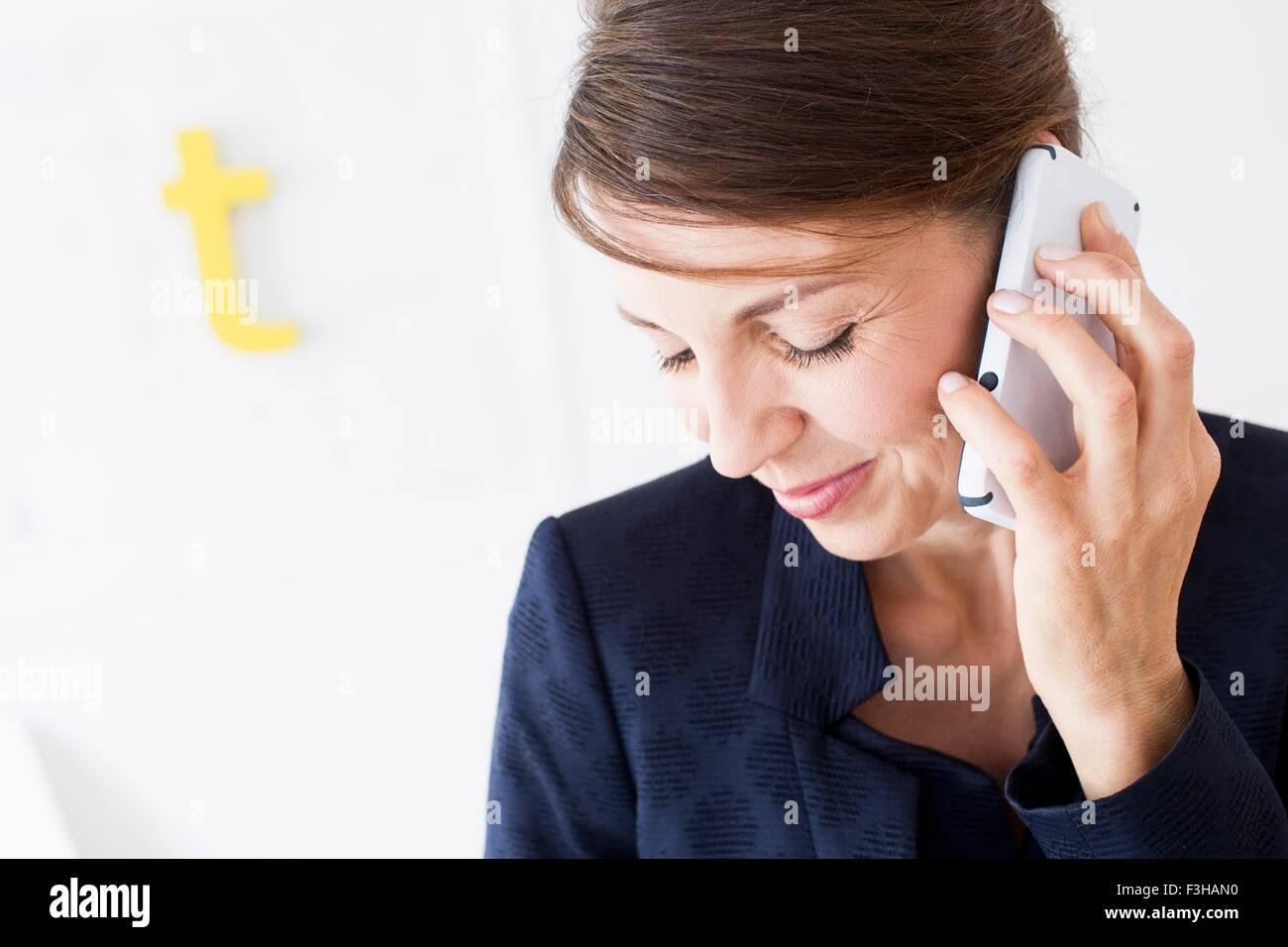Kopf und Schultern von Reife Frau mit Smartphone, blickte lächelnd Stockbild