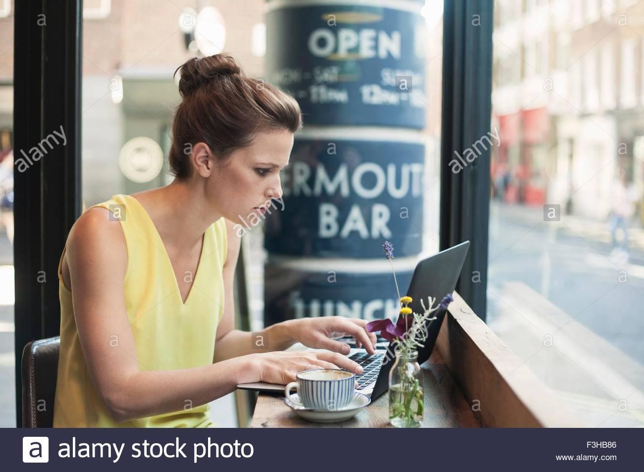 Eine junge Brünette Frau sitzt in einem café Stockbild